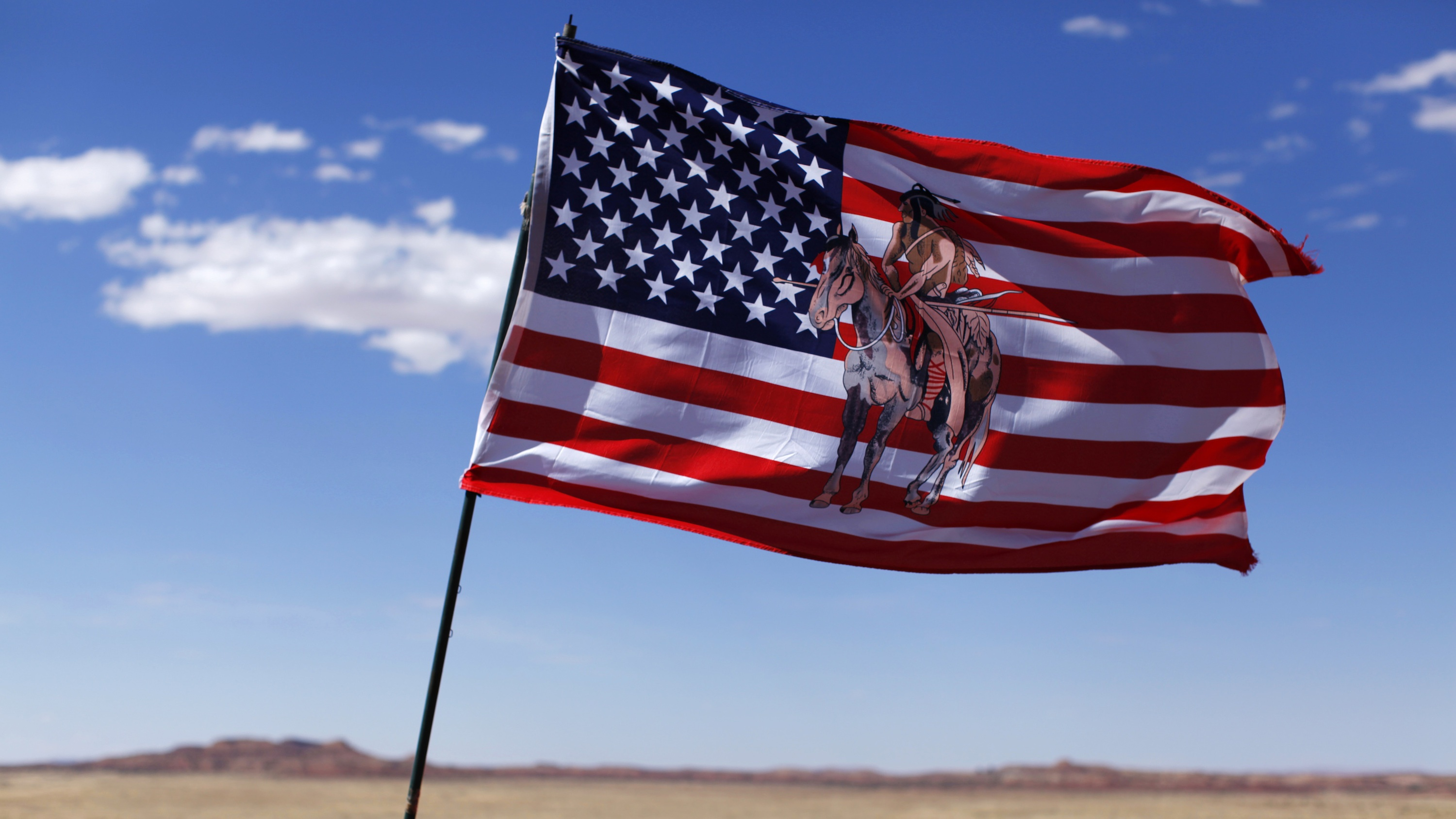 An embroidered American flag flies next to a jewelry stand on a Navajo reservation in Arizona.