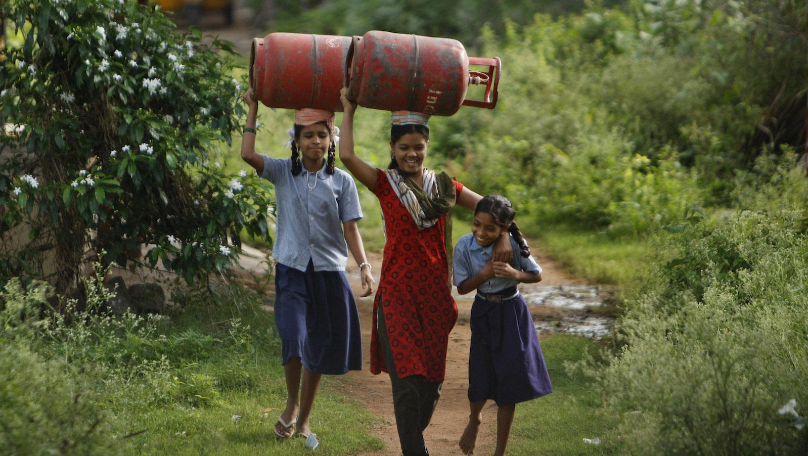 Indian girls share a light moment as they carry liquefied petroleum gas cylinders for cooking purposes in Hyderabad, India, Tuesday, Aug. 20, 2013. As part of its economic reform program, the Indian government last year announced a reduction in cooking gas subsidies. Currently each Indian household has been set a limit of nine subsidized refills a year.