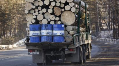 A truck carries wood and Gazprom Neft branded oil barrels.