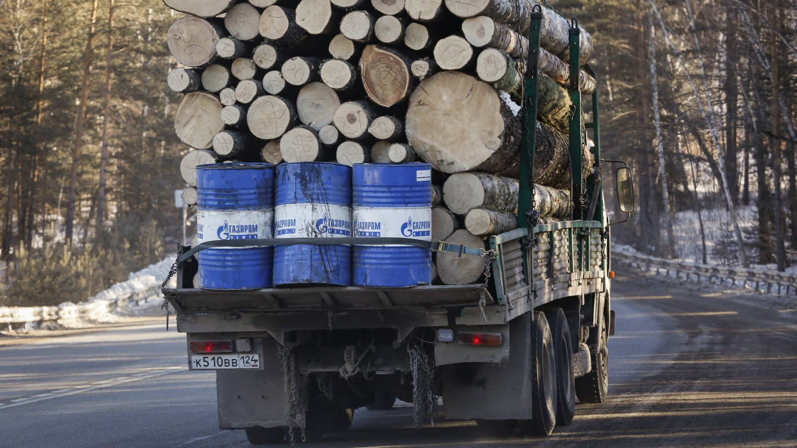 A truck carries wood and Gazprom Neft branded oil barrels along the M54 federal highway south of Siberian city of Krasnoyarsk, February 21, 2015. Picture taken February 21, 2015. REUTERS/Ilya Naymushin (RUSSIA - Tags: TRANSPORT ENERGY ENVIRONMENT BUSINESS INDUSTRIAL) - RTR4QL1K