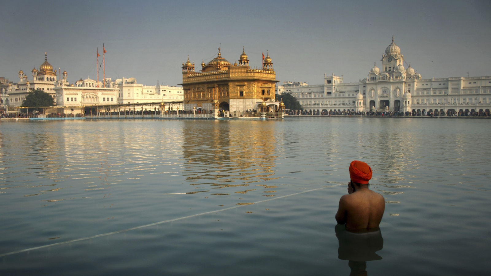 An Indian Sikh devotee takes a holy dip in the sacred pond at the Golden Temple in Amritsar, India, Wednesday, Jan. 1, 2014. Thousands of Sikh devotees stand in a queue to pay obeisance at the Golden Temple, Sikhs' holiest shrine, on the first day of the New Year.