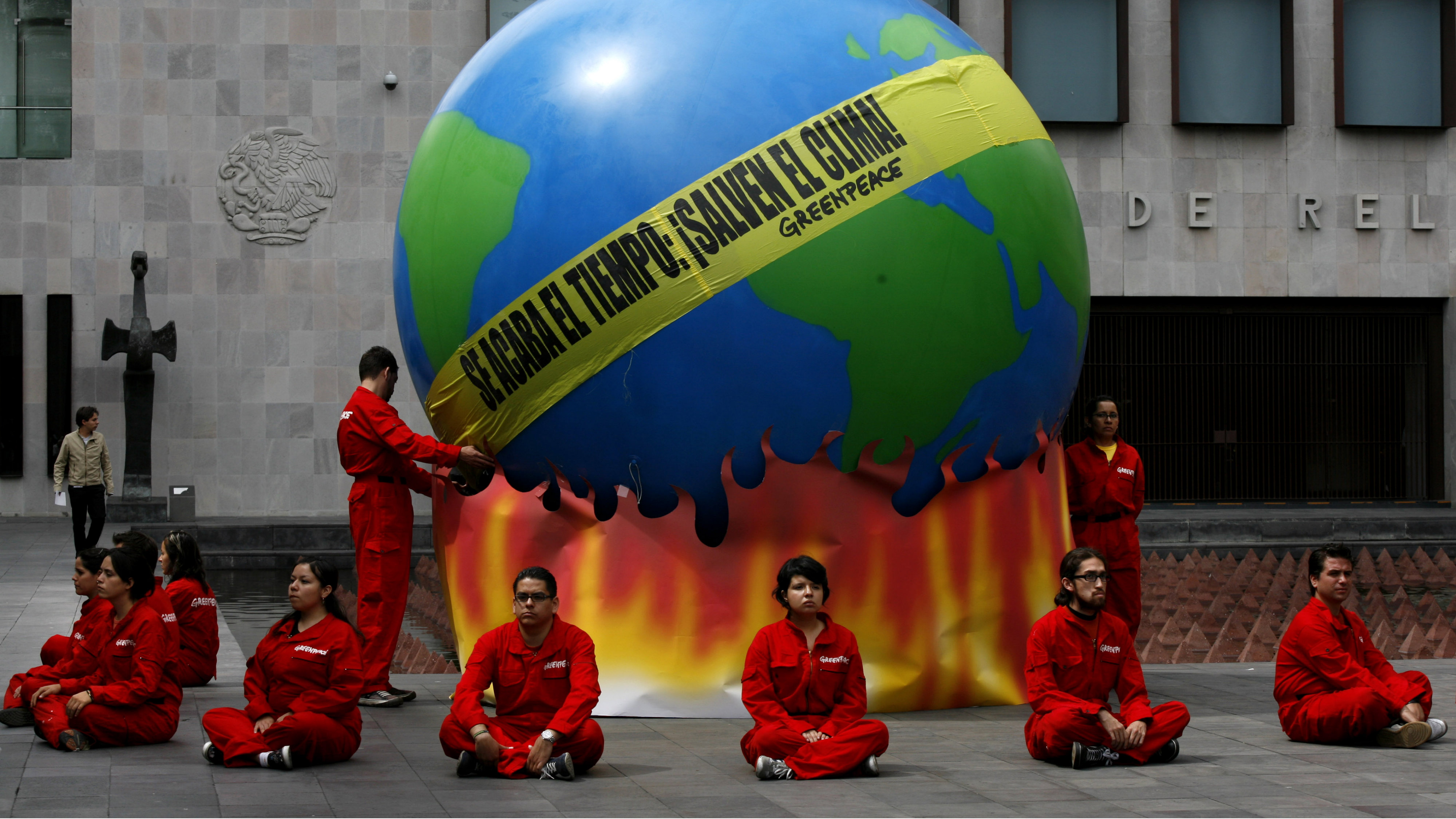 """Greenpeace activists stage a protest with an earth-shaped balloon in front of Mexico Secretary of Foreign Relations in Mexico City, Thursday Aug. 27, 2009. The protest was held to ask Mexican authorities to have a stronger position on global warming and climate change. Banner across the globe reads: """"Time is running out. Save the climate."""""""