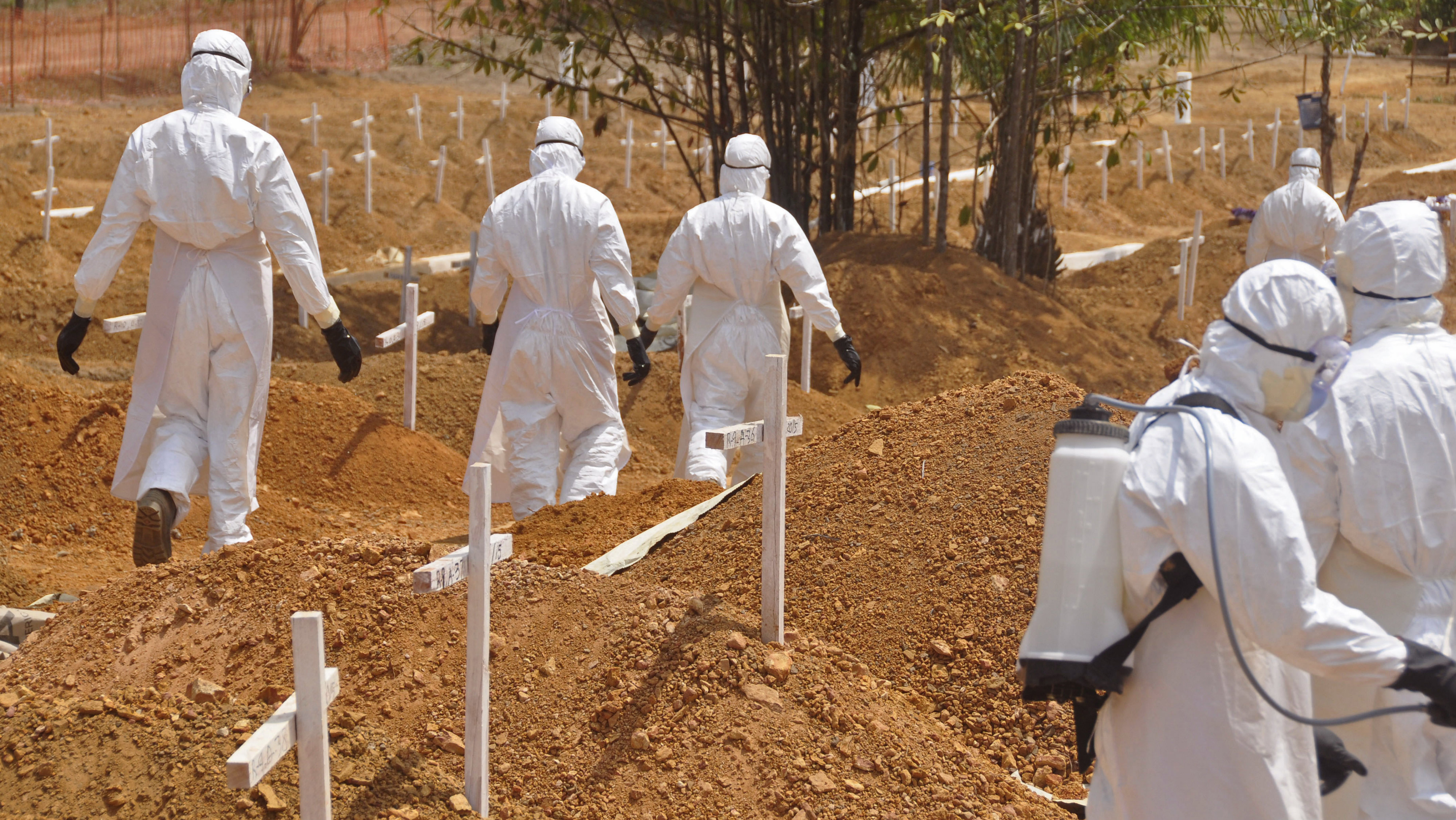 In this file photo dated Wednesday, March 11, 2015, health workers walk inside a new graveyard for Ebola victims, on the outskirts of Monrovia, Liberia. Despite the drop in reported Ebola cases, Dr. Bruce Aylward, leading WHO's Ebola response, declared Friday April 10, 2015, that it's too early for World Health Organization to downgrade the global emergency status of the biggest-ever Ebola outbreak in Africa.