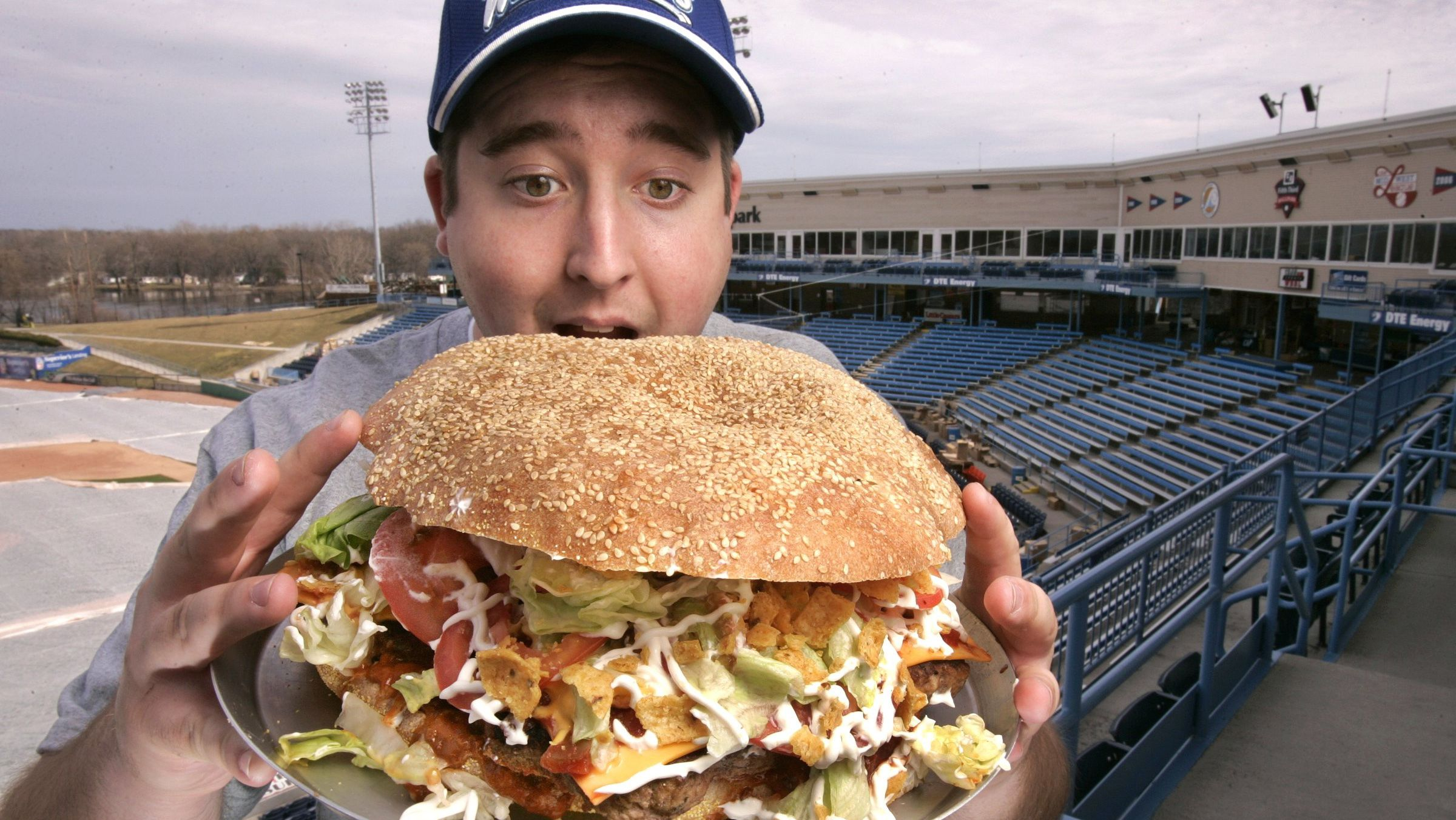 Josh Kowalczyk, an intern with the West Michigan Whitecaps, in Comstock Park, Mich. poses for a photo March 24, 2009. The $20 burger will feature a sesame-seed bun made from a pound of dough, five 1/3-pound beef patties, five slices of cheese, nearly a cup of chili and liberal doses of salsa and corn chips. (AP Photo/The Grand Rapids Press, Rex Larsen)