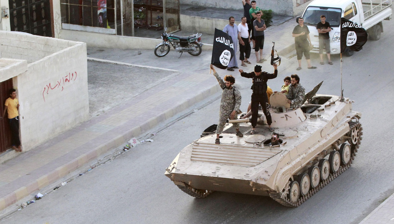 "Militant Islamist fighters take part in a military parade along the streets of northern Raqqa province June 30, 2014. Militant Islamist fighters held a parade in Syria's northern Raqqa province to celebrate their declaration of an Islamic ""caliphate"" after the group captured territory in neighbouring Iraq, a monitoring service said. The Islamic State, an al Qaeda offshoot previously known as Islamic State in Iraq and the Levant (ISIL), posted pictures online on Sunday of people waving black flags from cars and holding guns in the air, the SITE monitoring service said.  REUTERS/Stringer (SYRIA - Tags: POLITICS CIVIL UNREST CONFLICT) - RTR3WJ9Q"
