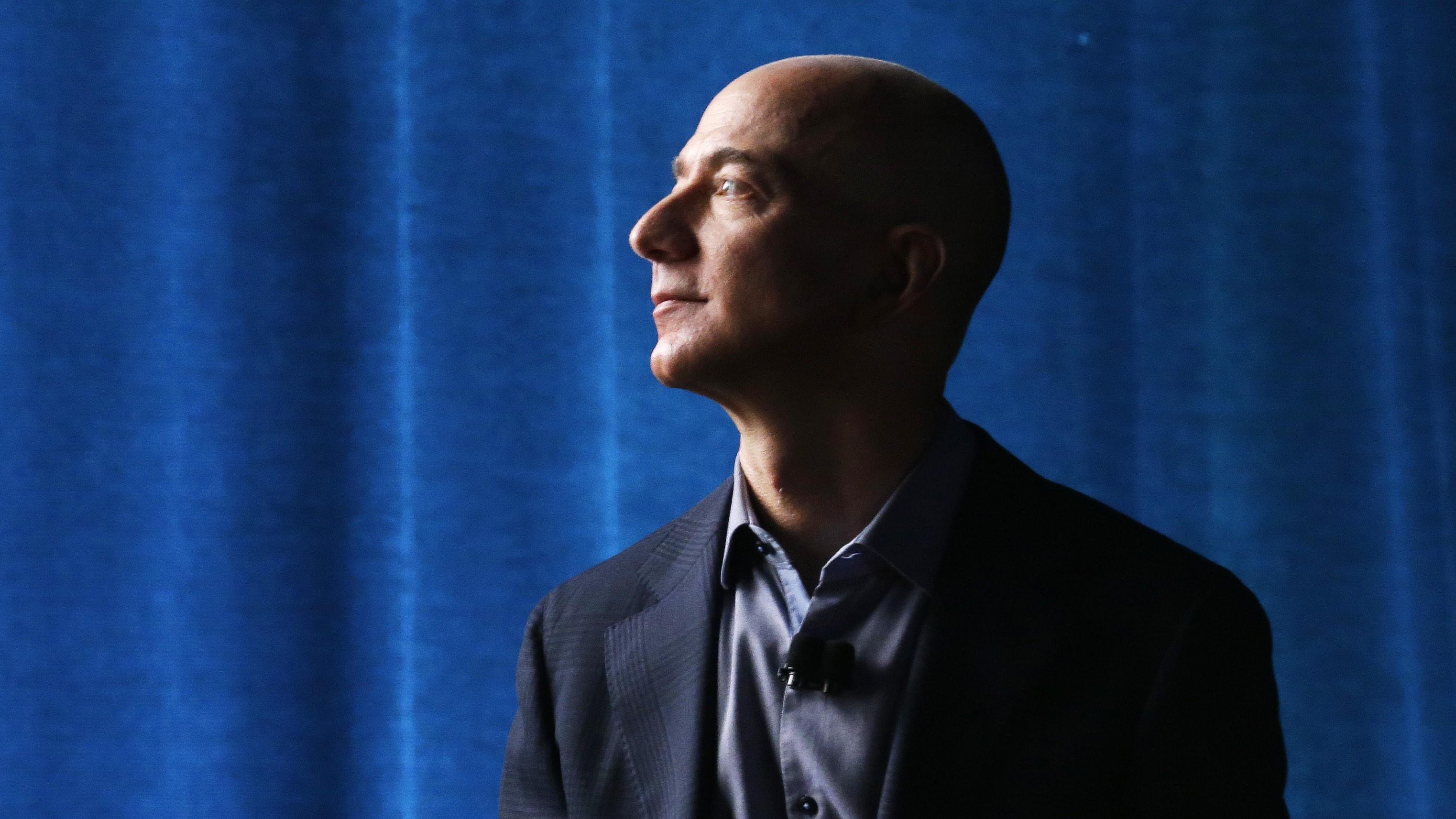 Amazon CEO Jeff Bezos watches a video presentation from the wings during the launch of the new Amazon Fire Phone, Wednesday, June 18, 2014, in Seattle.