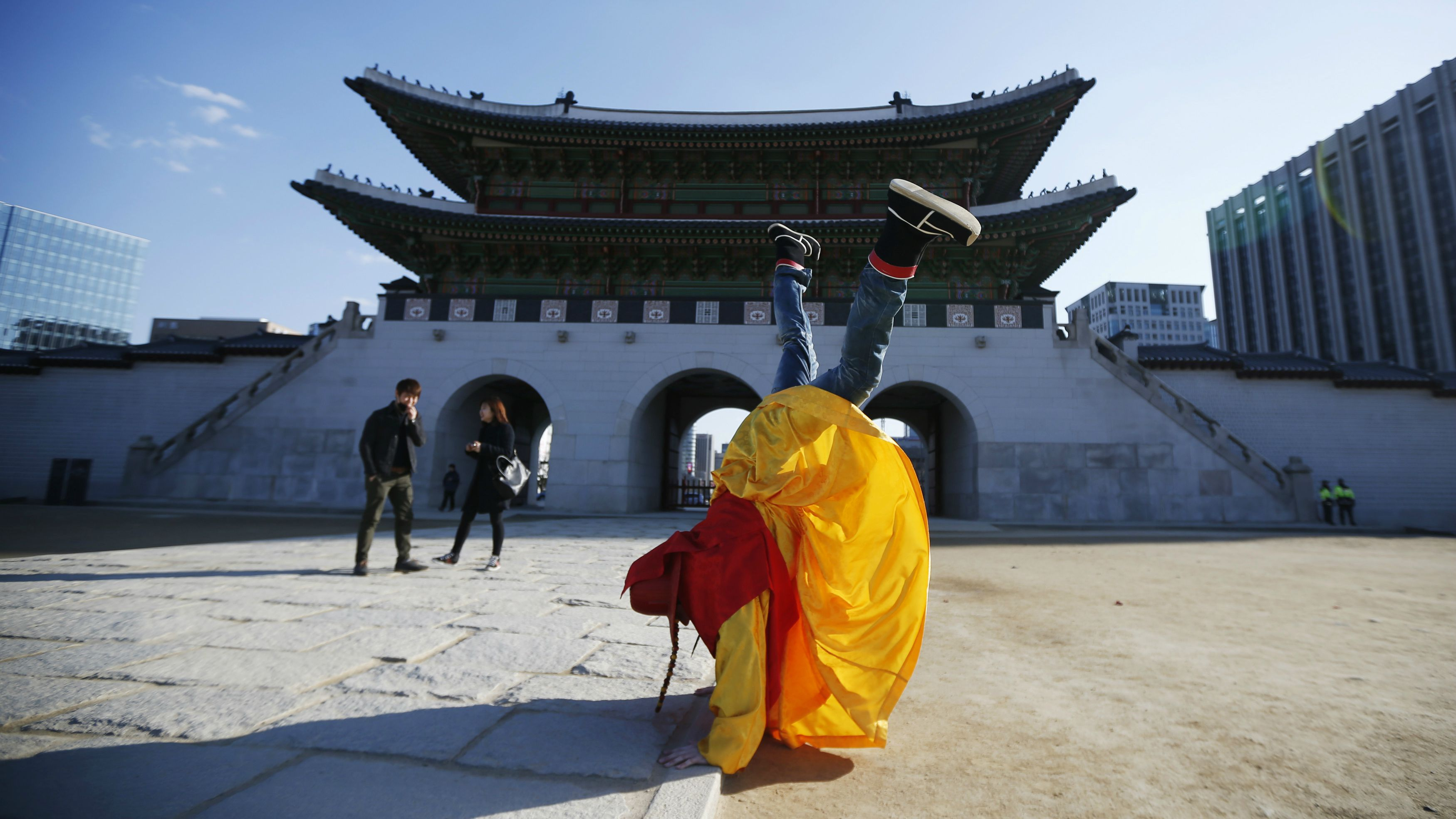 A tourist wearing a traditional costume stands on his hands to pose for a photograph in front of the main entrance of Gyeongbok palace on a sunny winter day in Seoul March 5, 2014. REUTERS/Kim Hong-Ji (SOUTH KOREA - Tags: SOCIETY TPX IMAGES OF THE DAY TRAVEL)