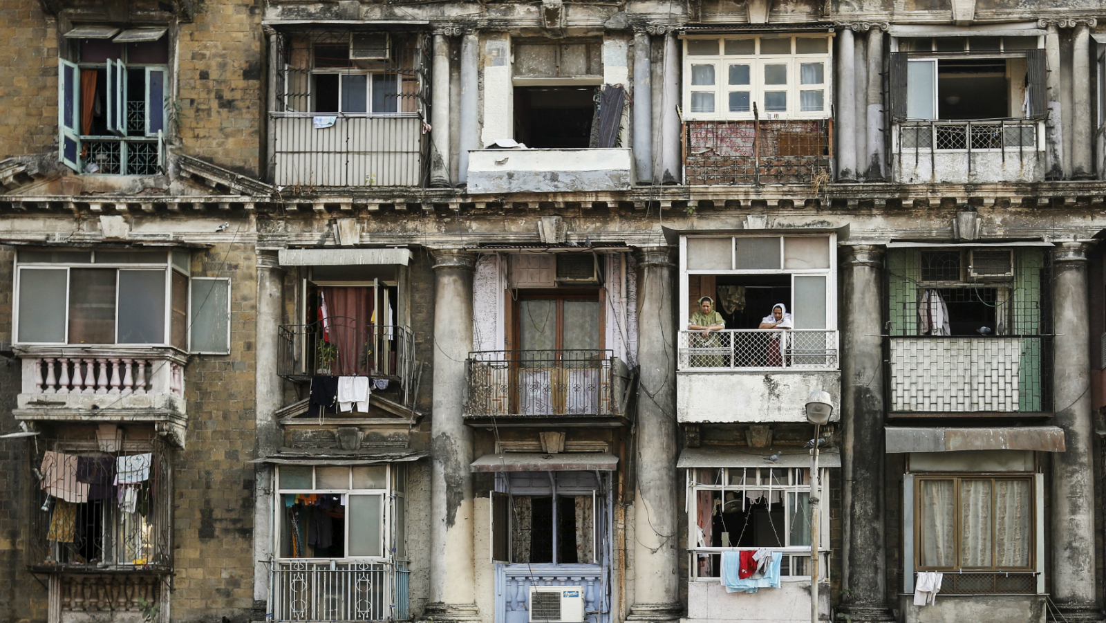 Residents look out of a window of an apartment in south Mumbai February 19, 2014. The cost for buying a 600 square feet (55 square meters) one-bedroom apartment in this building is around 14,166 Indian rupees ($225) per square feet or 8,500,000 Indian rupees ($136,000). The rent for an apartment in the same building is around 20,000 Indian rupees ($320) per month. REUTERS/Danish Siddiqui