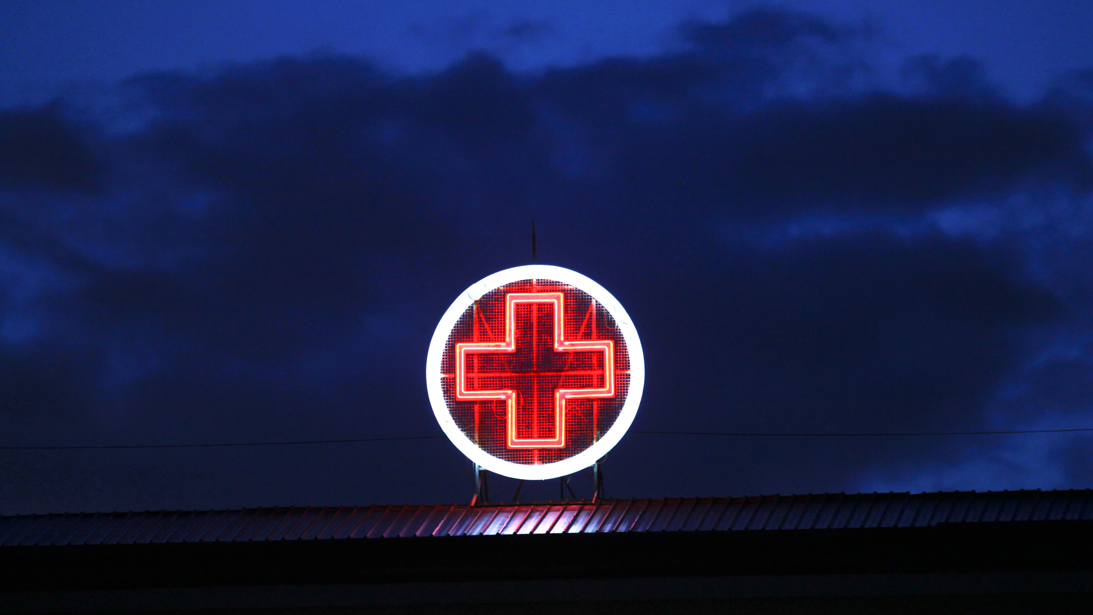 A red neon cross is seen on the rooftop of the Evangelismos State General Hospital in Athens May 30, 2012. Greece's rundown state hospitals are cutting off vital drugs, limiting non-urgent operations and rationing even basic medical materials for exhausted doctors as a combination of economic crisis and political stalemate strangle health funding. With Greece now in its fifth year of deep recession, trapped under Europe's biggest public debt burden and dependent on international help to keep paying its bills, the effects are starting to bite deeply into vital services. Picture taken May 30, 2012.
