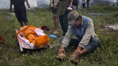 A man sits next to the body of a victim of Saturday's earthquake, before cremation at the Pashupatinath temple, on the banks of Bagmati river, in Kathmandu, Nepal, Sunday, April 26, 2015. The earthquake centered outside Kathmandu, the capital, was the worst to hit the South Asian nation in over 80 years. It destroyed swaths of the oldest neighborhoods of Kathmandu, and was strong enough to be felt all across parts of India, Bangladesh, China's region of Tibet and Pakistan.(AP Photo/Bernat Armangue)