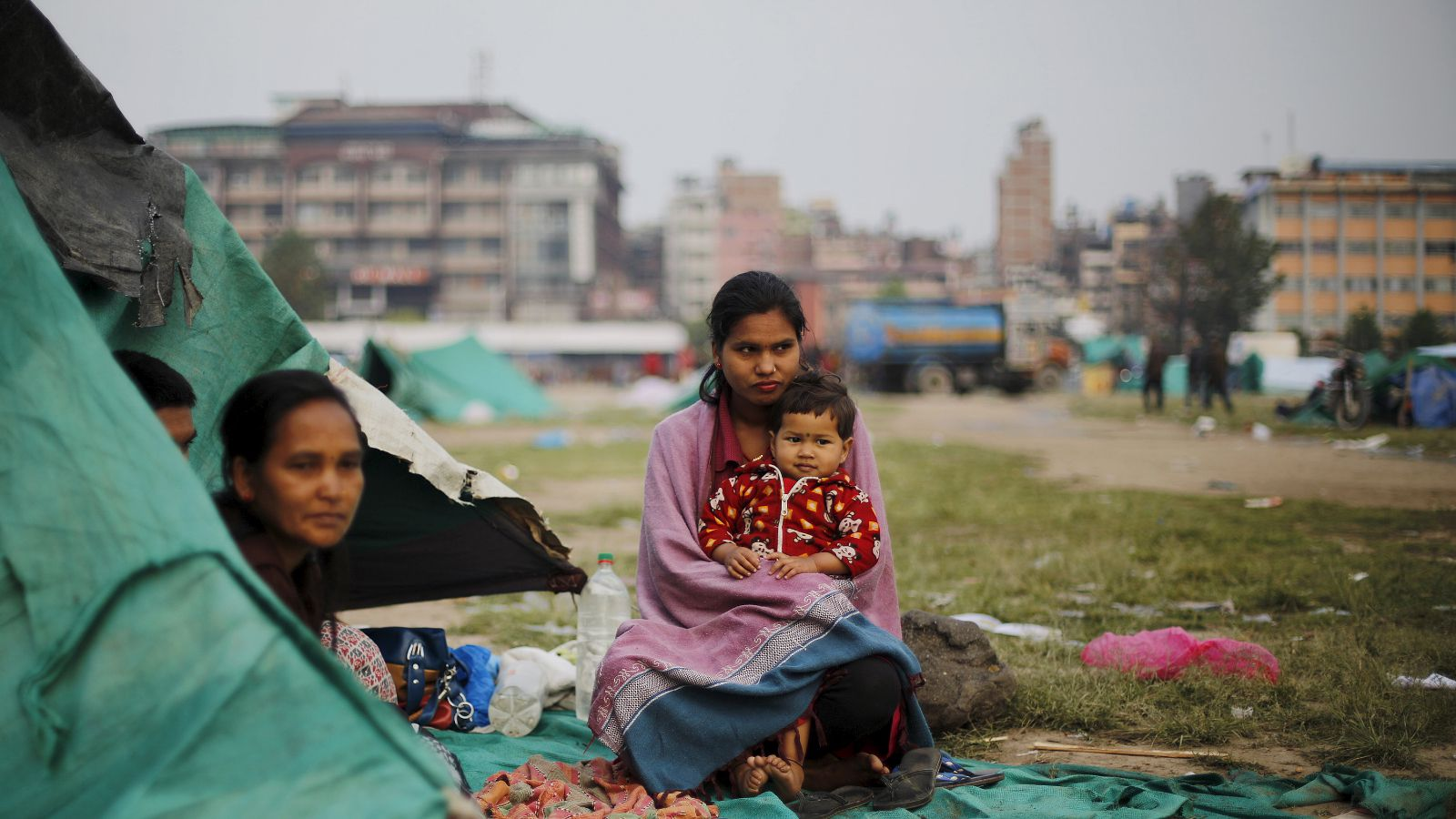An earthquake victim holds her daughter as she sits outside her makeshift shelter on open ground in the early hours in Kathmandu, Nepal April 28, 2015.