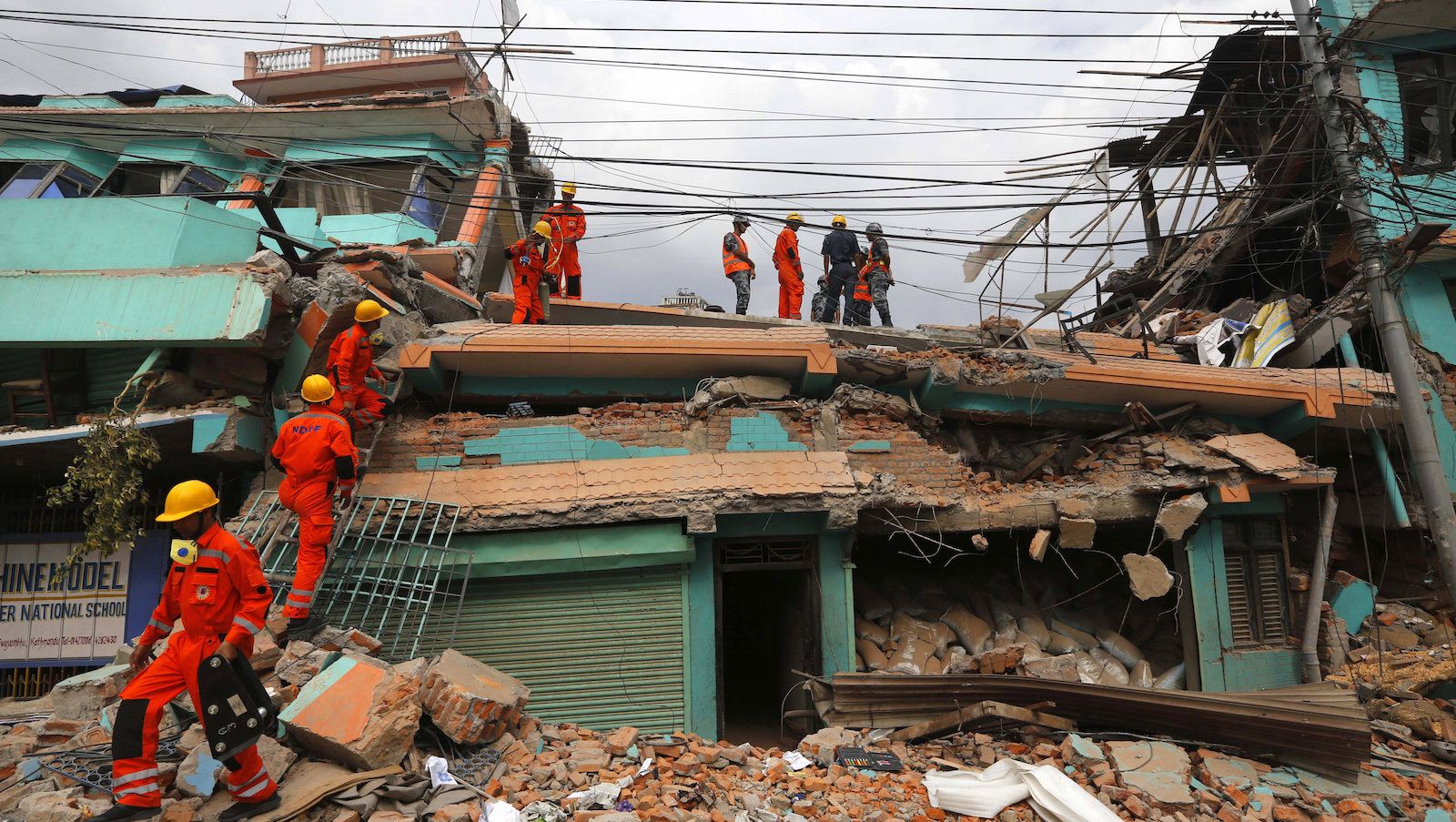 India's National Disaster Response Force personnel look for survivors in a building, in Kathmandu, Nepal, Sunday, April 26, 2015. Sleeping in the streets and shell-shocked, Nepalese cremated the dead and dug through rubble for the missing Sunday, a day after a massive Himalayan earthquake devastated the region and destroyed homes and infrastructure.