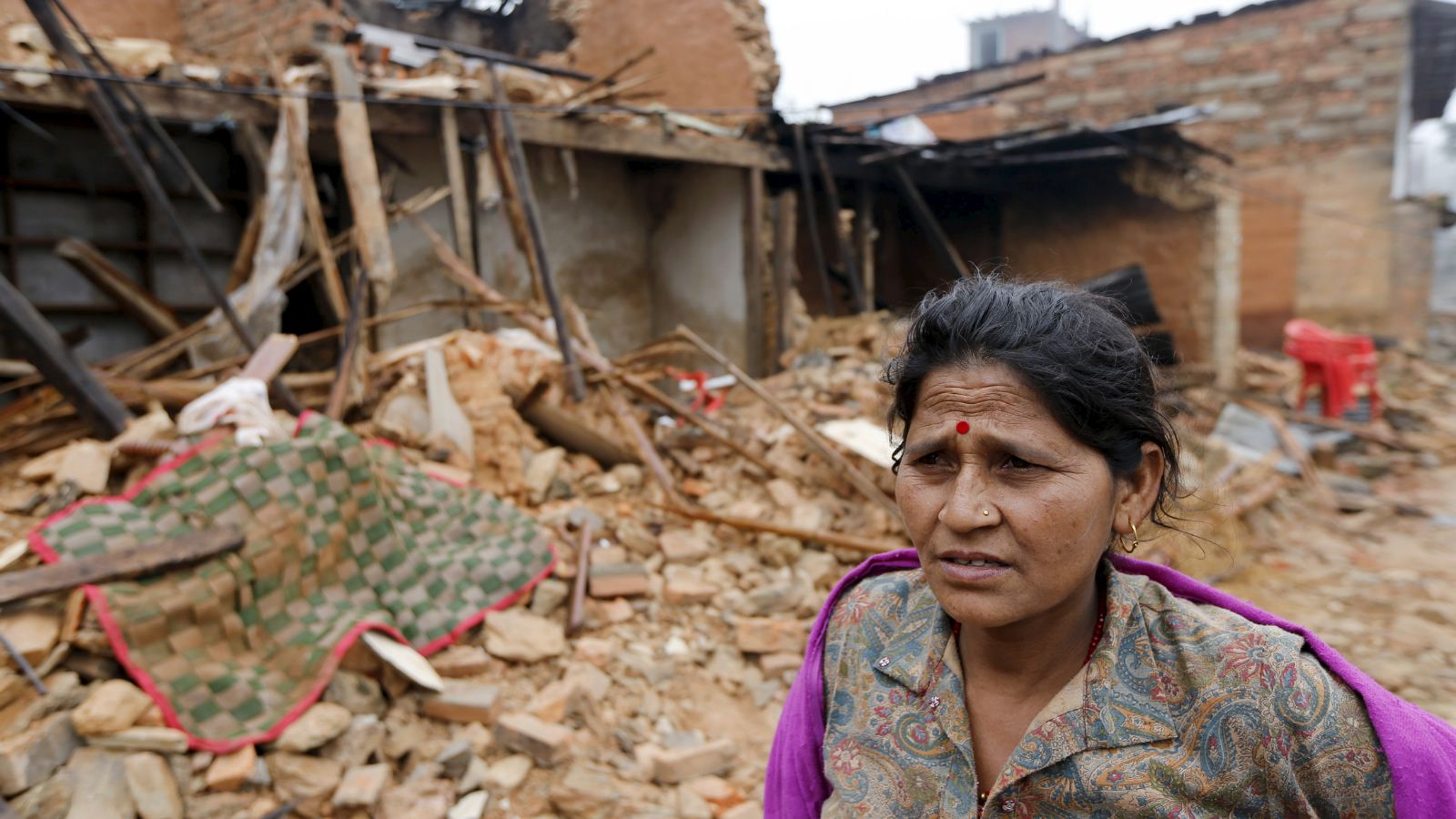 A Nepali woman stands in front of the wreckage of her house that was completely destroyed in Saturday's earthquake in Gorkha, Nepal, April 30, 2015.