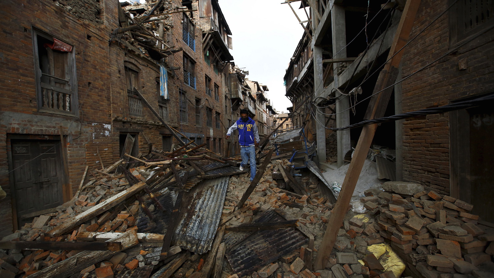 A man walks along the collapsed houses after the earthquake in Bhaktapur, Nepal April 27, 2015. Nepalese officials scrambled on Monday to get aid from the main airport to people left homeless and hungry by a devastating earthquake two days earlier, while thousands tired of waiting fled the capital Kathmandu for the surrounding plains. By afternoon, the death toll from Saturday's 7.9 magnitude earthquake had climbed to more than 3,700, and reports trickling in from remote areas suggested it would rise significantly.