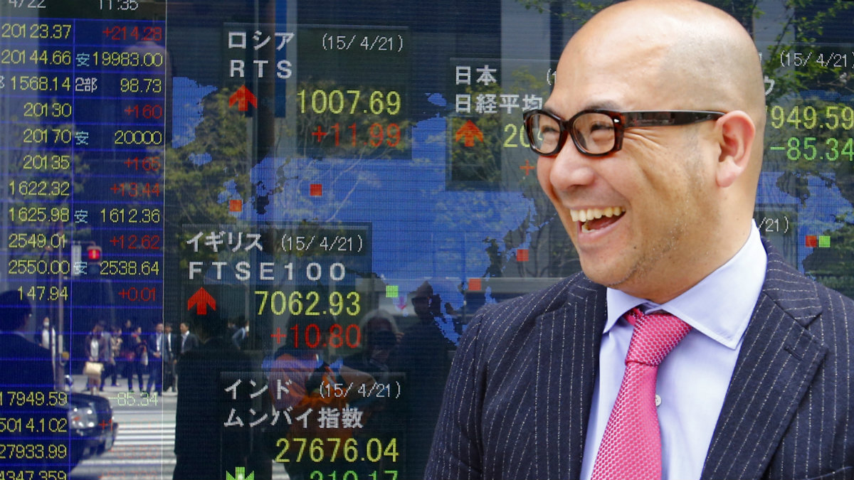 A man smiles in front of an electronic stock indicator of a securities firm in Tokyo, Wednesday, April 22, 2015. Asian stocks were mostly higher Wednesday after Japan reported its first trade surplus in three years, adding optimism to regional sentiment despite a fall on Wall Street. Japan's benchmark Nikkei 225 added 1.1 percent to 20,123.37. (AP Photo/Shizuo Kambayashi)