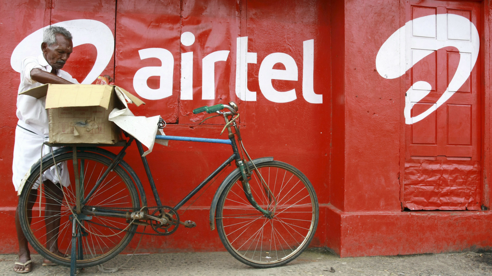 A man packs goods on the back of his bicycle as he stands next to the wall of a grocery shop painted with an advertisement for Bharti Airtel in the southern Indian city of Kochi May 5, 2011. The loss-making African operation of Bharti Airtel Ltd is expected to suppress near-term earnings of India's biggest mobile operator, which posted a bigger-than-expected 31.5 percent net profit drop in the March quarter. REUTERS/Sivaram V (INDIA - Tags: BUSINESS)