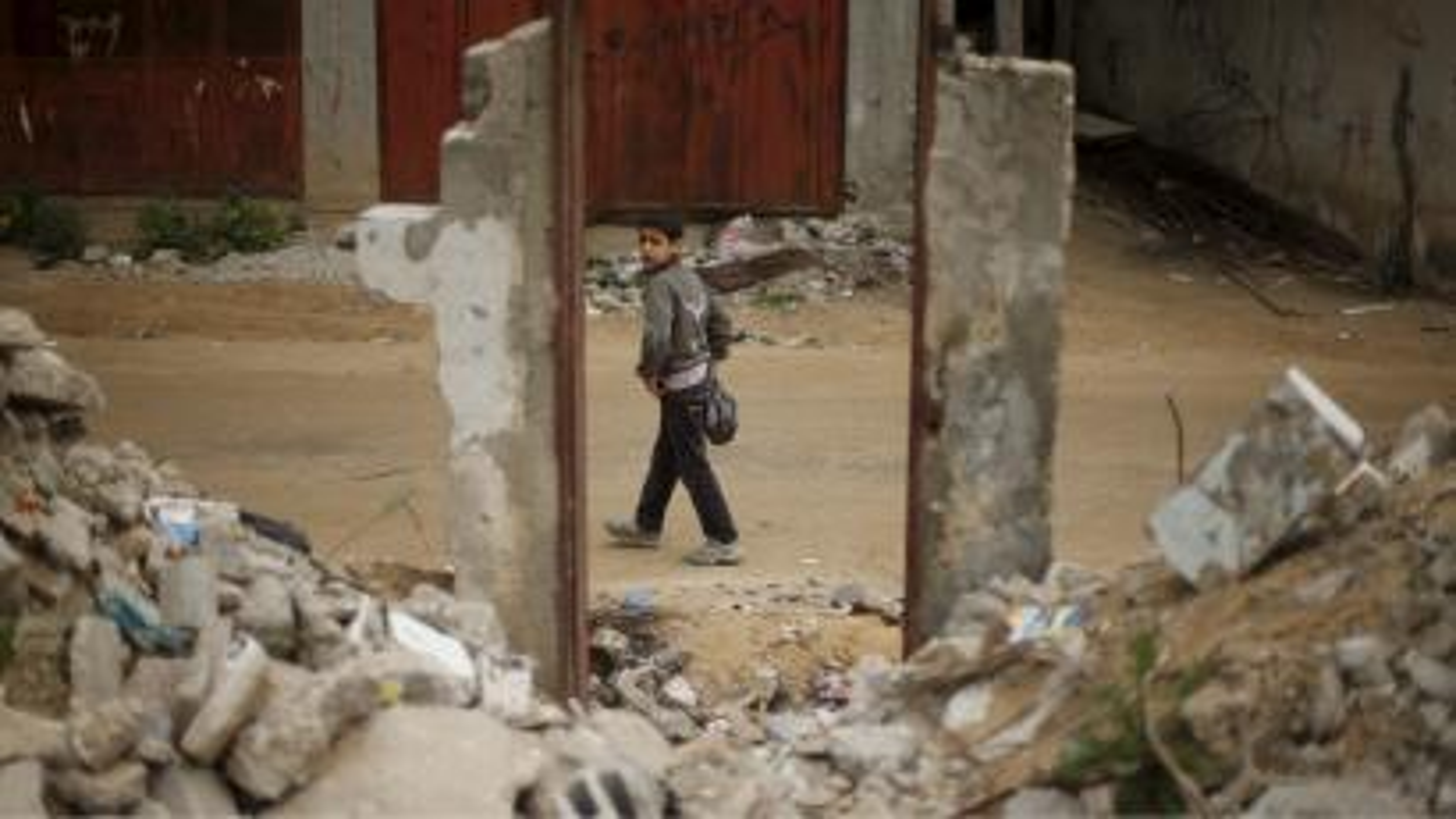 palestinian boy near destroyed building