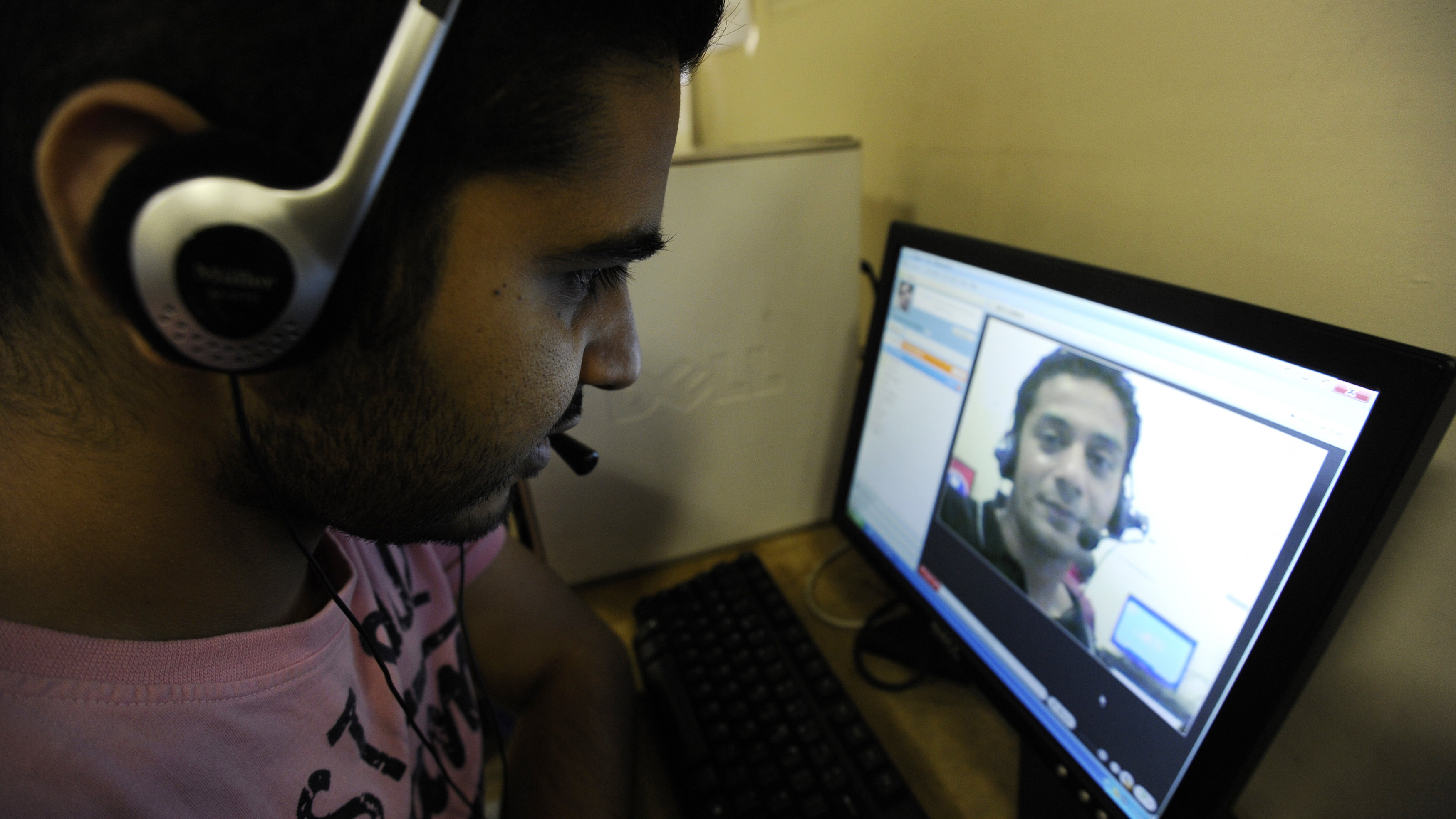 Zubair Ghumro (L) speaks to his friend Sheeraz Qazalbash using Skype software at an internet cafe in central London August 10, 2010. Internet phone services provider Skype filed to raise up to $100 million through an IPO, hoping that its wide name recognition and rapid growth will outweigh concerns that few of its customers actually pay.
