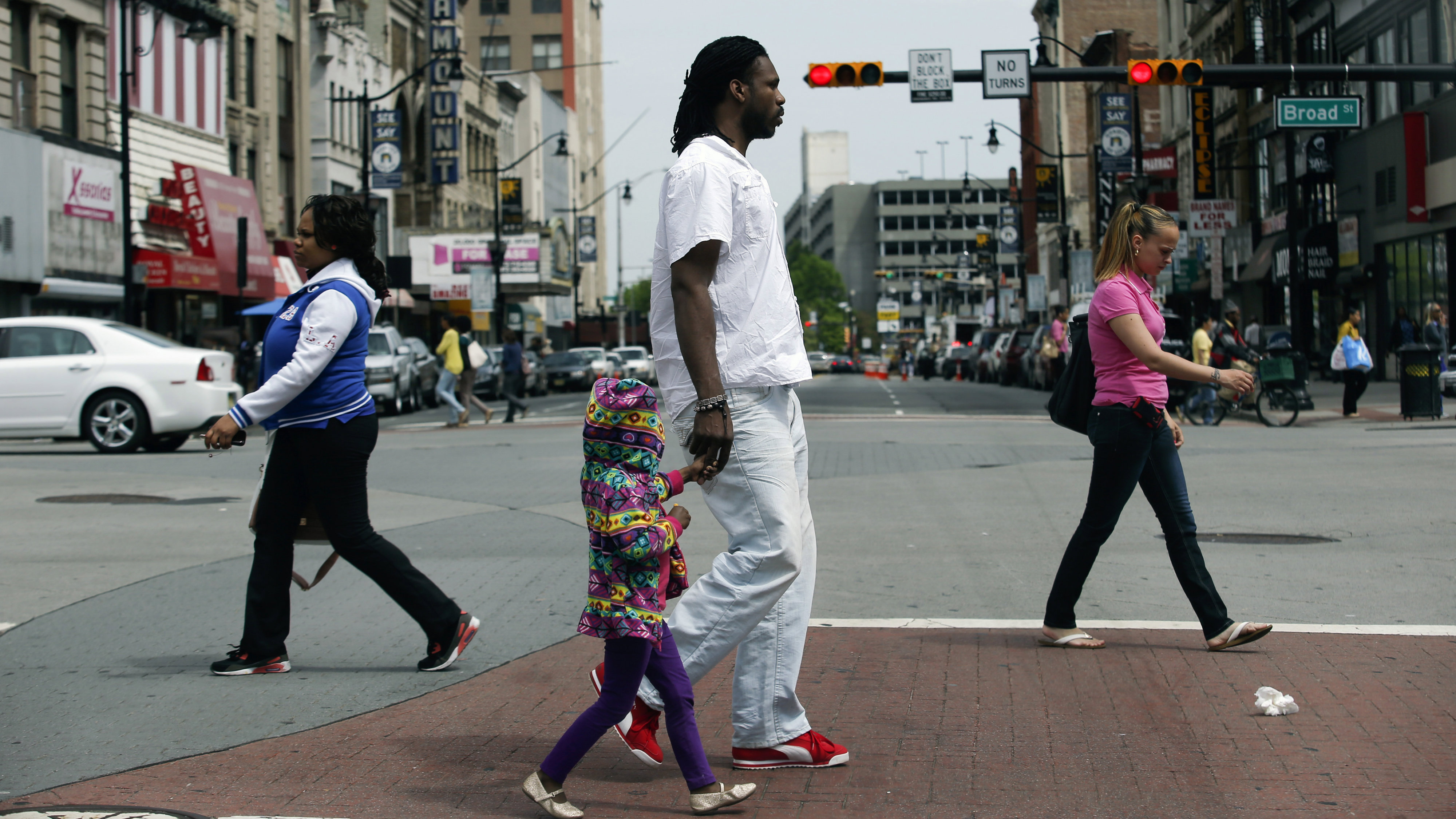 People cross a street during mayoral elections in Newark, New Jersey, May 13, 2014. Voters in Newark will pick a new mayor on Tuesday to fill a post held by popular Democrat Cory Booker and steer New Jersey's largest city as it struggles with an uptick in violent crime, unemployment and a possible state takeover of its finances.