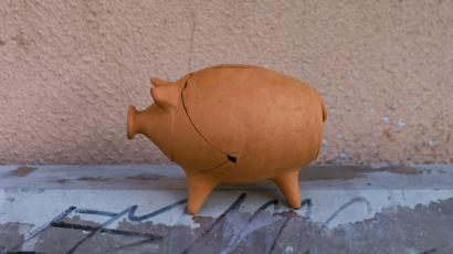 A cracked-open and reassembled piggy bank rests on top of an electricity box in Lisbon, Portugal.