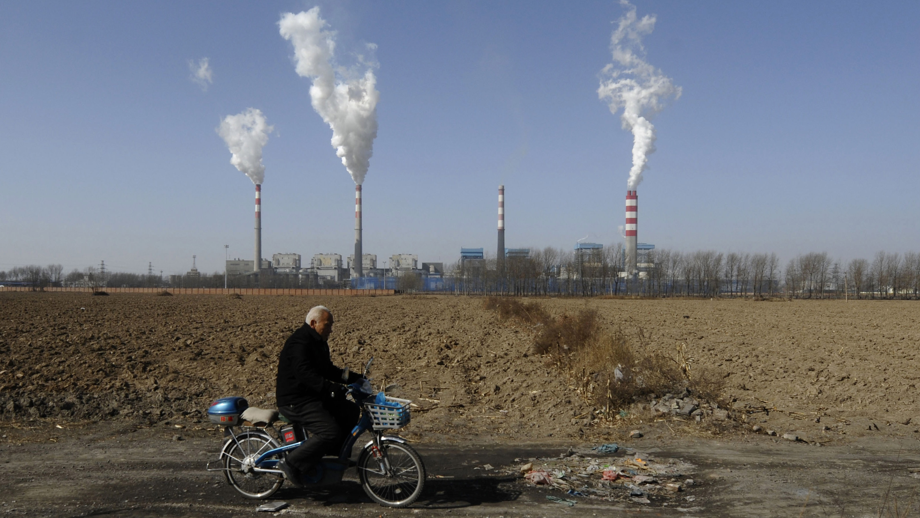 A man rides on a road near a power plant on the outskirts of Changzhi, Shanxi province February 20, 2009. The global financial crisis will not affect China's resolve to tackle global warming, the Foreign Ministry said on Thursday, ahead of a visit to Beijing by U.S. Secretary of State Hillary Clinton.