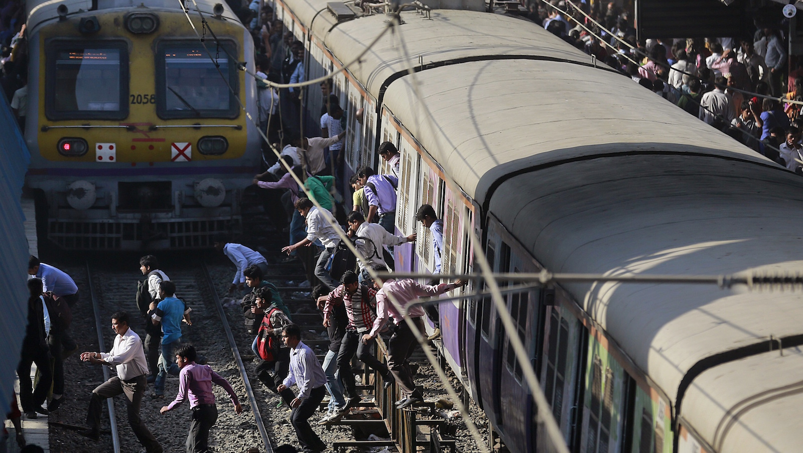 Commuters cross railway tracks to catch trains at a railway station in Mumbai, India, Thursday, Feb. 26, 2015. Indian Railway minister Suresh Prabhu will unveil the Rail Budget 2015 on Thursday for one of the world's largest railways systems that serves more than 23 million passengers a day.