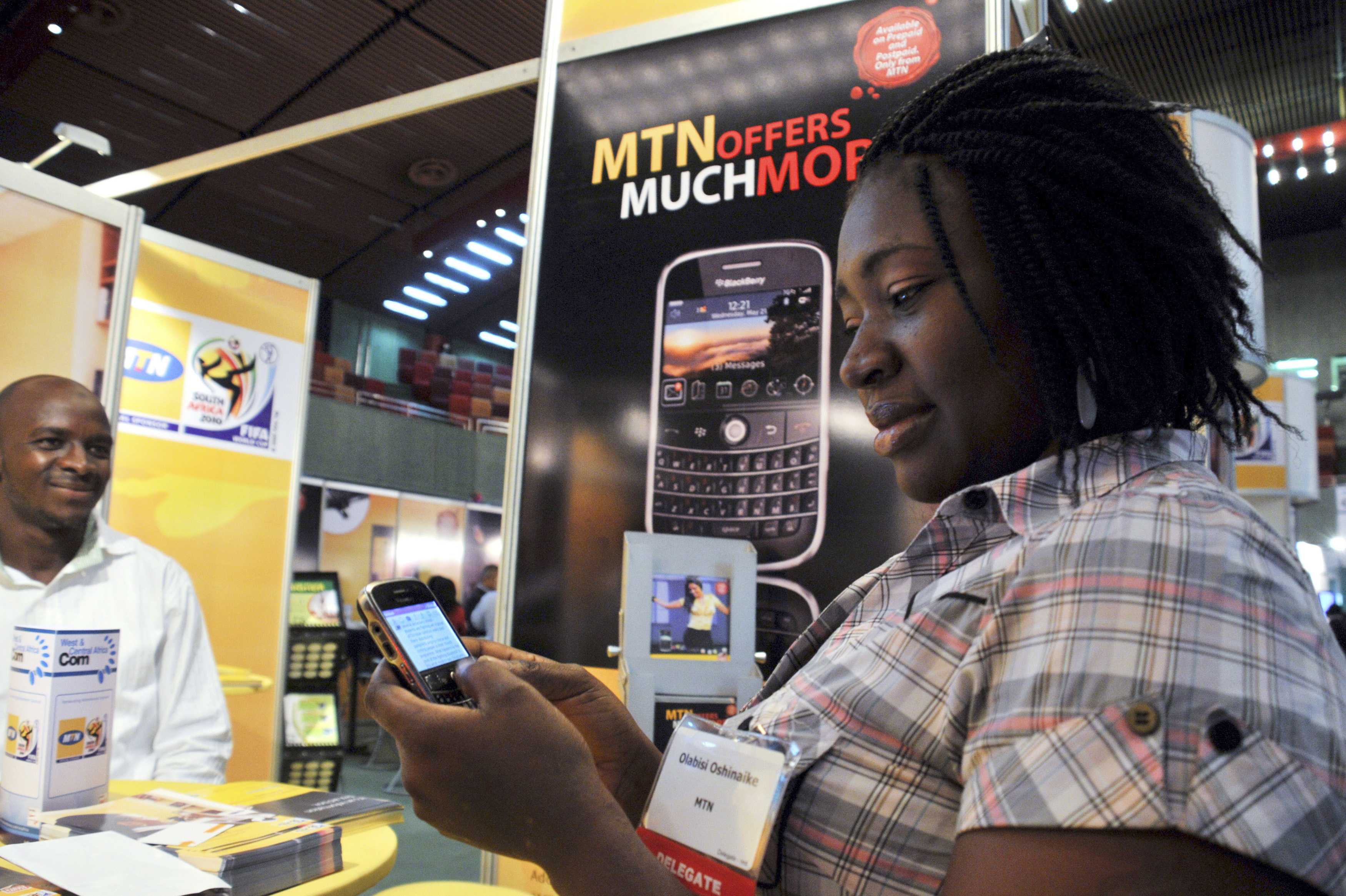 A delegate checks a blackberry handset at an exhibition stand during the West & Central Africa Com conference in Nigeria's capital Abuja, June 18, 2009. Nigeria's mobile subscriber base is growing at around the fastest pace since the advent of GSM technology at the start of the decade, but average revenue per user is tailing off, industry analysts said on Wednesday.   REUTERS/Afolabi Sotunde (NIGERIA BUSINESS SCI TECH) - RTR24SIM