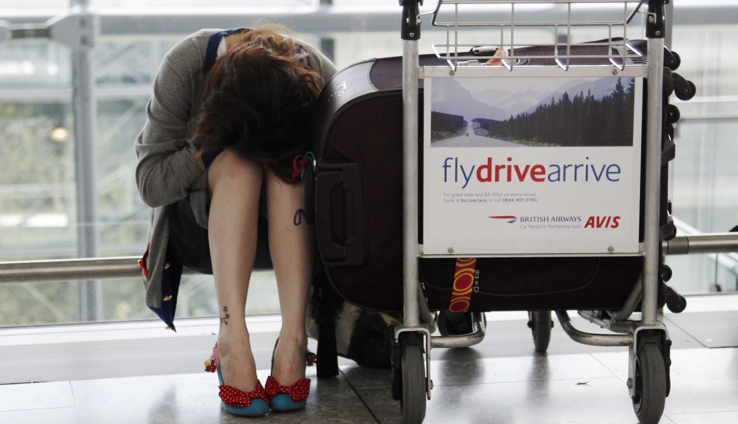 A traveller rests with her luggage as flights are delayed and cancelled at Heathrow Airport in London May 17, 2010. Volcanic ash from Iceland grounded 1,000 flights and delayed hundreds of thousands of passengers in parts of northern Europe on Monday. Several of Europe's busiest airports, including London's Heathrow and Schiphol in Amsterdam, were closed for several hours due to fears the ash could damage jet engines and bring down aircraft.       REUTERS/Luke MacGregor (BRITAIN - Tags: TRANSPORT ENVIRONMENT EMPLOYMENT BUSINESS TRAVEL SOCIETY) - RTR2DZYF