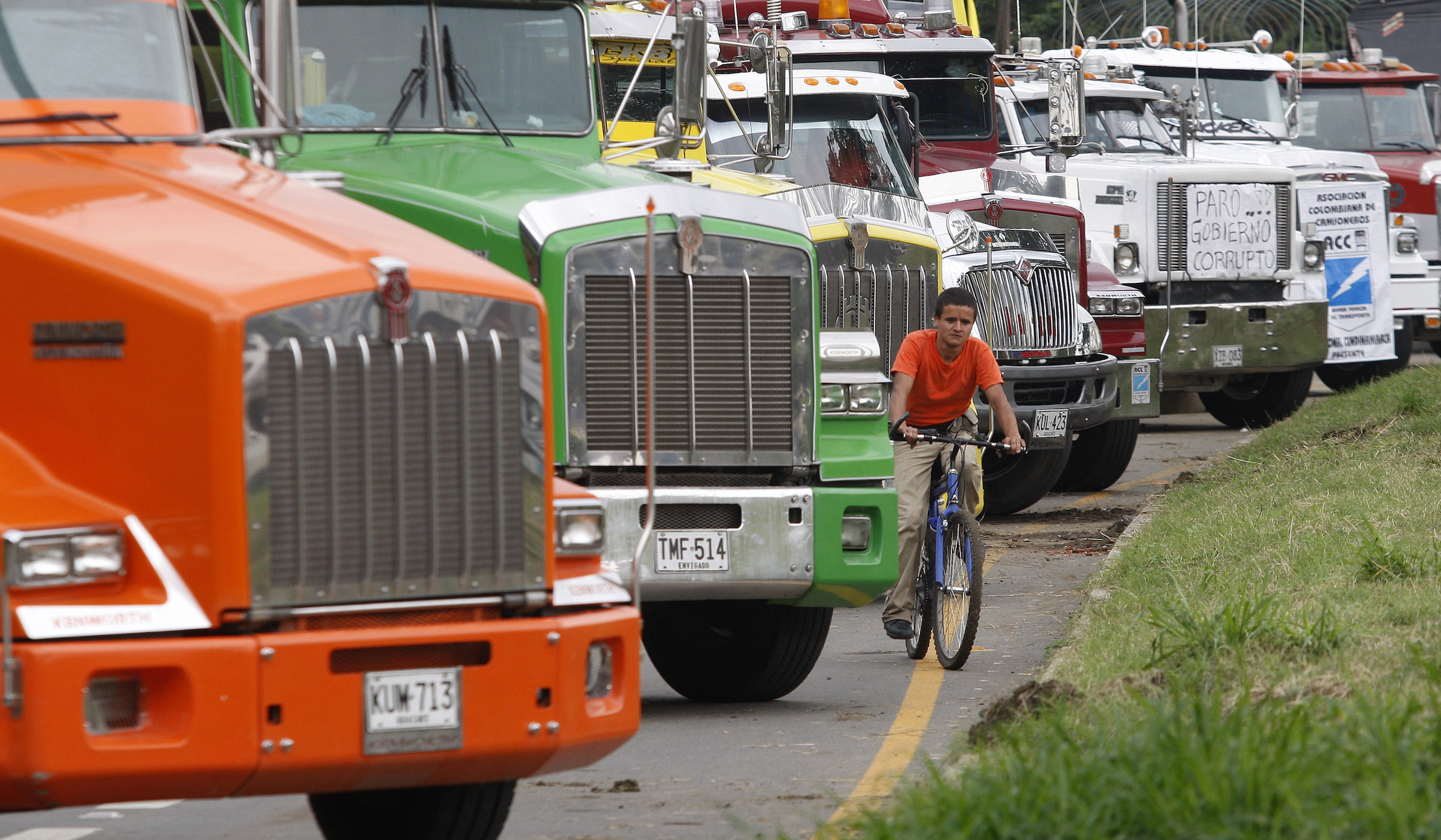 A man rides a bicycle in between trucks during a transporters' strike in Yumbo near Cali February 17, 2011. Tens of thousands of truckers in Colombia went on strike since February 3 over a move by the government to eliminate minimum freight rates, prompting fears of a hit to exports such as coffee if the strike prolongs. REUTERS/Jaime Saldarriaga (COLOMBIA - Tags: TRANSPORT CIVIL UNREST BUSINESS POLITICS) - RTR2IQUE