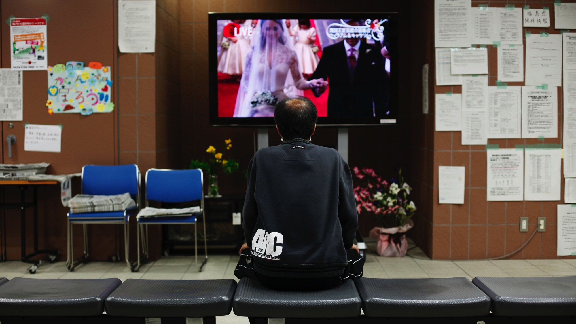Hajime Ajima, an evacuee of the March 11 earthquake and tsunami, watches a TV broadcast of the wedding of Britain's Prince William and Kate Middleton in London, at a gymnasium converted into an evacuation center, inside Ajinomoto stadium in Chofu, western Tokyo April 29, 2011. (ROYAL WEDDING/PUBLIC)  REUTERS/Toru Hanai (JAPAN - Tags: DISASTER ROYALS ENTERTAINMENT SOCIETY) - RTR2LR6N