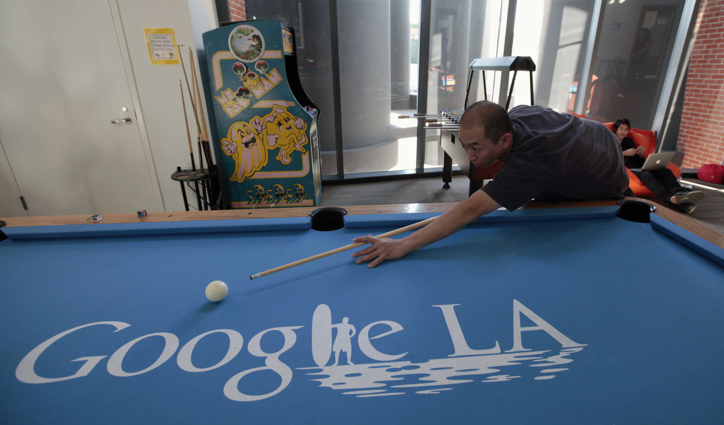 An employee plays pool at the Google campus near Venice Beach, in Los Angeles, California January 13, 2012. The 100,000 square-foot campus was designed by architect Frank Gehry, and includes an entrance through an iconic pair of giant binoculars designed by Claes Oldenburg and Coosje van Bruggen. Around 500 employees develop video advertising for YouTube, parts of the Google+ social network and the Chrome Web browser at the site. REUTERS/Lucy Nicholson (UNITED STATES - Tags: SCIENCE TECHNOLOGY BUSINESS SOCIETY) - RTR2W9CE
