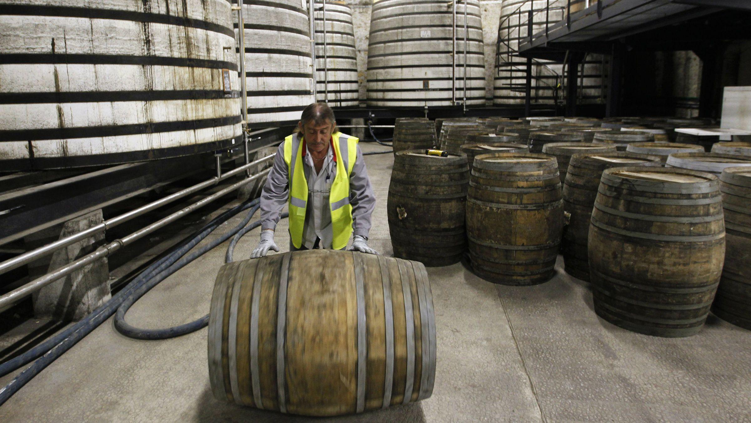 A technician rolls an oak barrel in a cellar where cognac is aged at the Remy Martin distillery in Cognac, southwestern France.