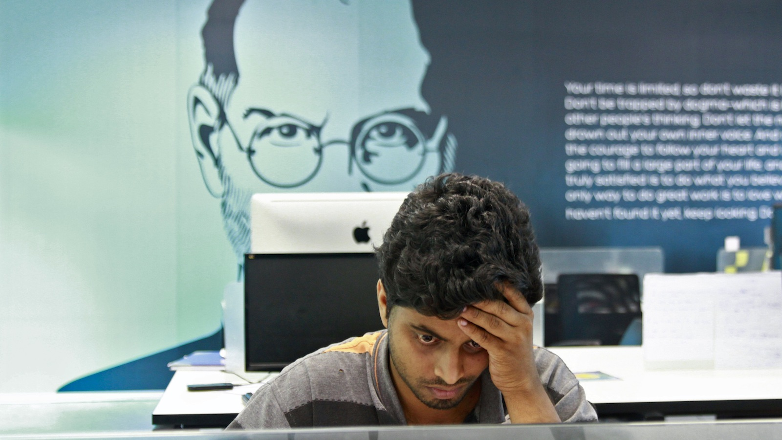 An employee works on a computer terminal against the backdrop of a picture of late Apple co-founder Steve Jobs at the Start-up Village in Kinfra High Tech Park in the southern Indian city of Kochi October 13, 2012. Three decades after Infosys, India's second-largest software service provider, was founded by middle-class engineers, the country has failed to create an enabling environment for first-generation entrepreneurs. Startup Village wants to break the logjam by helping engineers develop 1,000 Internet and mobile companies in the next 10 years. It provides its members with office space, guidance and a chance to hobnob with the stars of the tech industry. But critics say this may not even be the beginning of a game-changer unless India deals with a host of other impediments - from red tape to a lack of innovation and a dearth of investors - that are blocking entrepreneurship in Asia's third-largest economy.