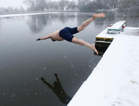 A swimmer dives into the men's pond as snow falls on Hampstead Heath