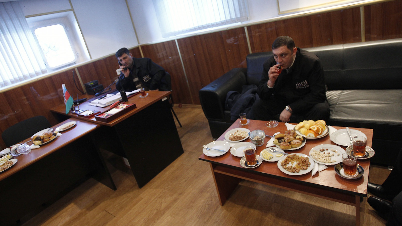 Oil worker Namik Aliyev (R) drinks a cup of tea during a short break as his chief Anar Jafarov speaks on the phone on an oil platform in Caspian Sea, about 100 km (62 miles) east of  Baku, January 22, 2013. Aliyev, 32, like the country of Azerbaijan itself, has oil in his blood. His father and grandfather both worked in oil production, an industry which dates back to the 19th century in Azerbaijan and contributes more than half of the country's gross domestic product (GDP).  Picture taken January 22, 2013. REUTERS/David Mdzinarishvili (AZERBAIJAN - Tags: ENERGY ENVIRONMENT BUSINESS SOCIETY)  ATTENTION EDITORS: PICTURE 16 OF 26 FOR PACKAGE 'OIL IN THE BLOOD' SEARCH 'BAKU OIL' FOR ALL IMAGES - RTR3DC4D