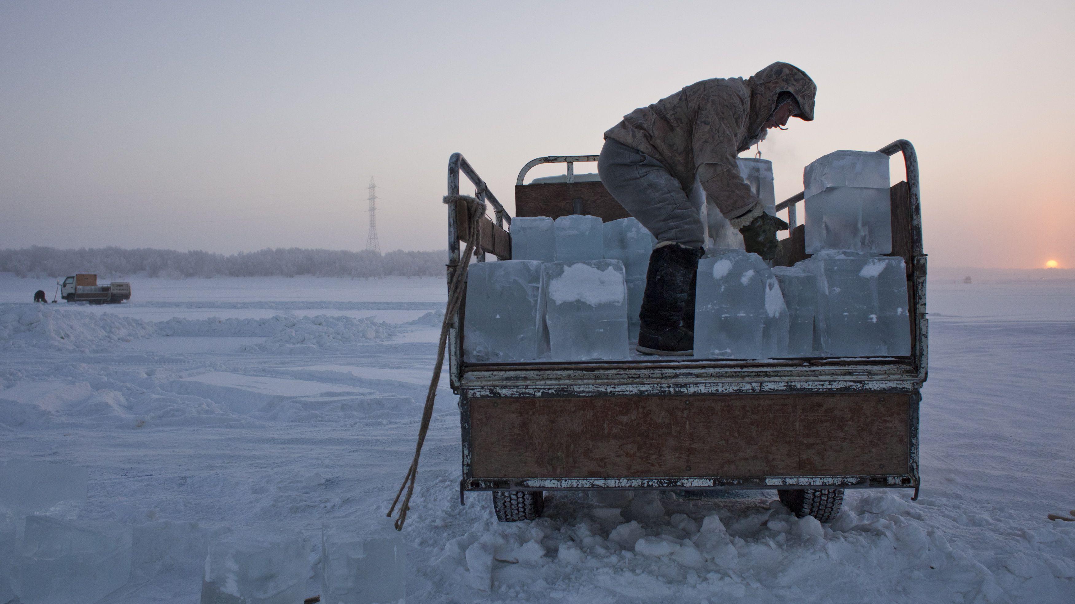 A man blocks of ice onto a truck outside Yakutsk