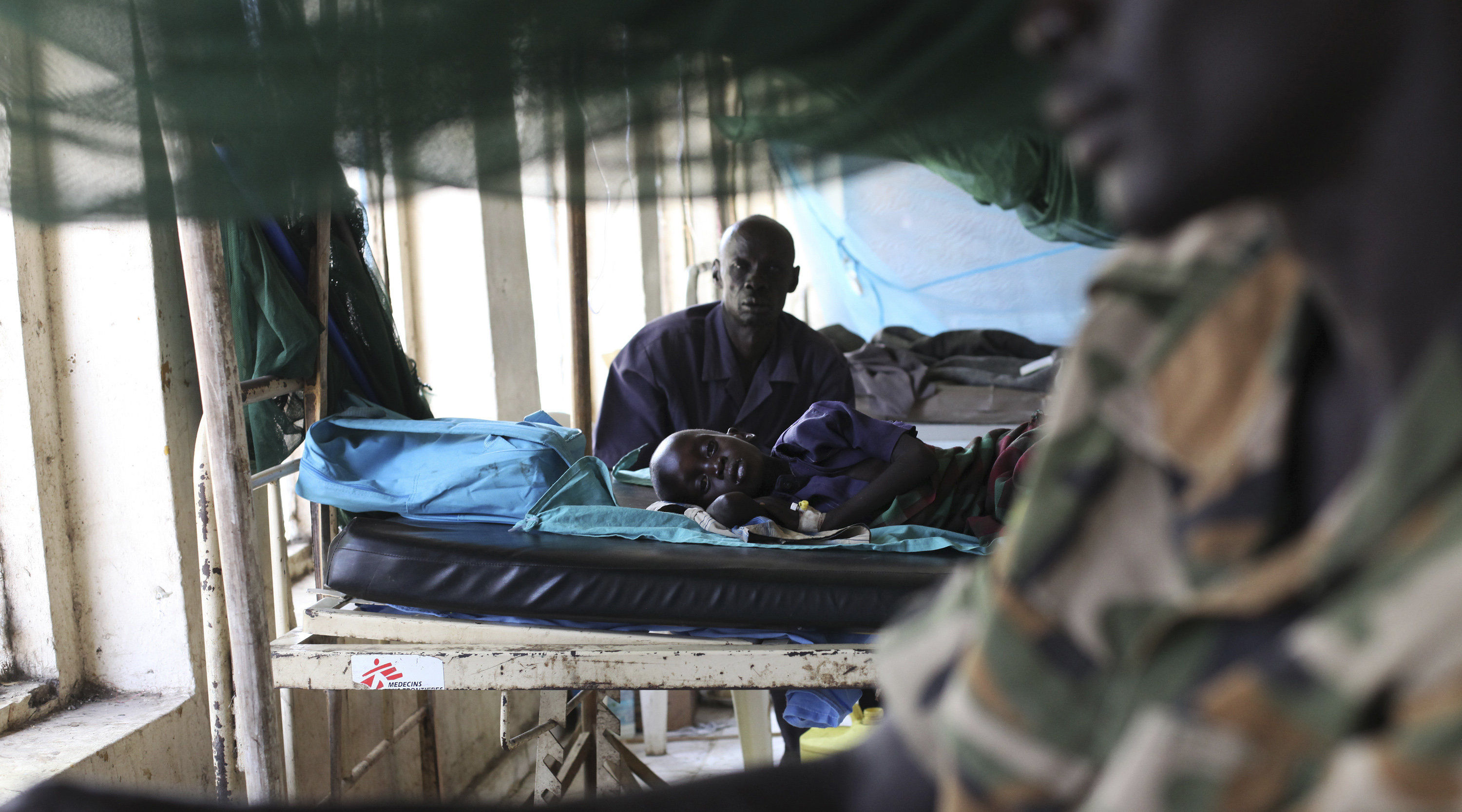 A child sick with malaria and from malnutrition lies on a bed in a hospital in Bor March 15, 2014.