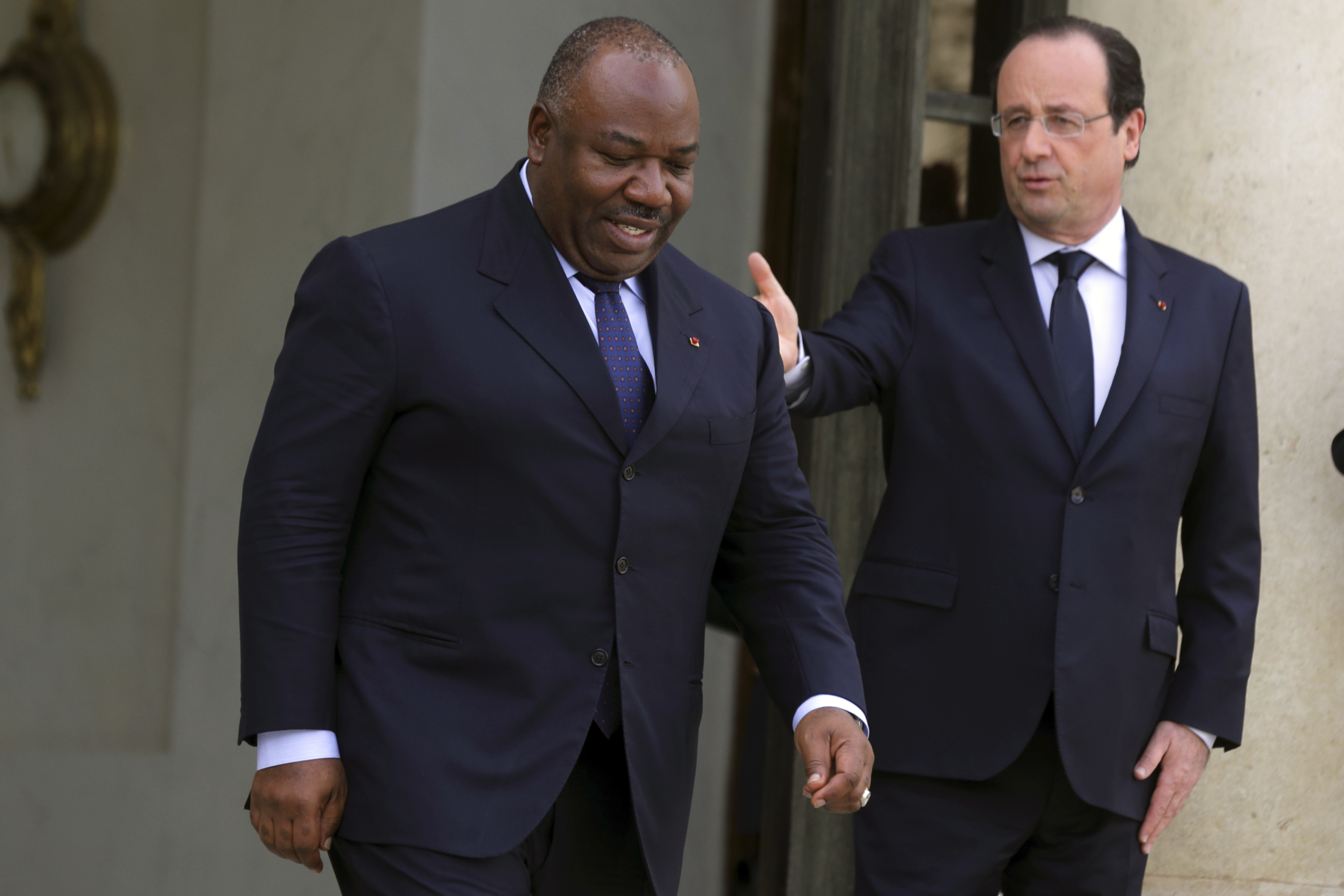 French President Francois Hollande (R) accompanies Gabon's President Ali Bongo Ondimba as he leaves the Elysee Palace in Paris, April 8, 2014. REUTERS/Philippe Wojazer (FRANCE - Tags: POLITICS) - RTR3KE5N
