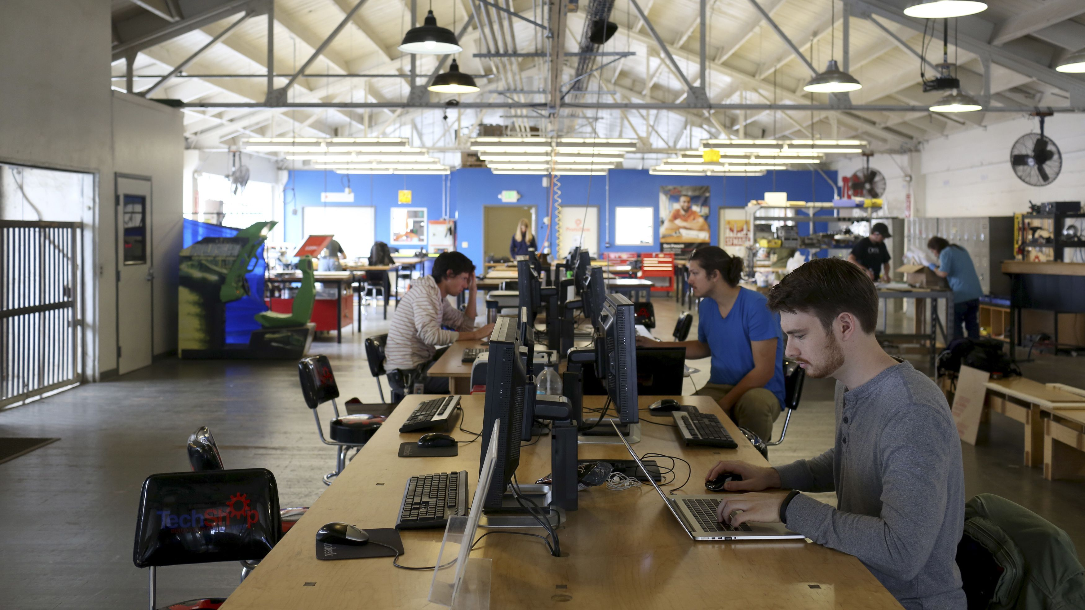 """Designers work at computer stations at TechShop in the South of Market neighborhood in San Francisco, California April 24, 2014. In the shadow of Internet monoliths, it's easy to forget that Silicon Valley got its start from hard-scrabble tinkerers building radios, microchips and other devices. Now, a proliferation of high-tech but affordable manufacturing tools and new sources of funding are empowering a generation of handy entrepreneurs and laying the foundation for a hardware renaissance. A growing focus on hardware and the so-called """"Maker movement"""" is sweeping northern California and, in a smaller way, Europe and other countries. Renewed interest in tinkering with objects - versus apps or software - is attracting more money from investors and fostering a growing number of workshops, where aspiring inventors can get their hands on computerized milling machines and other high-end tools. Picture taken April 24, 2014.   REUTERS/Robert Galbraith  (UNITED STATES - Tags: BUSINESS SCIENCE TECHNOLOGY) - RTR3NZ5R"""