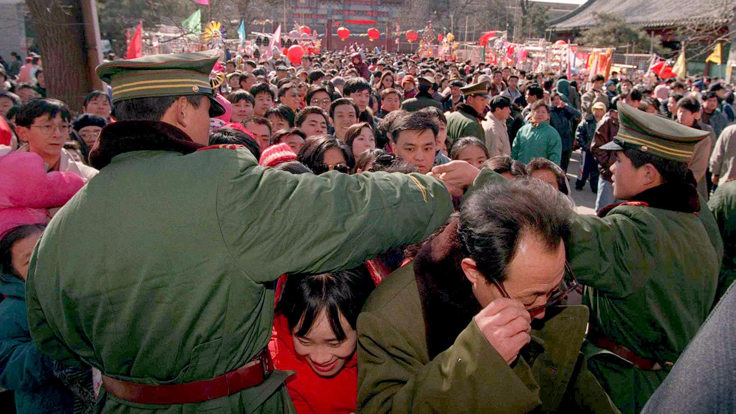 Police link arms to form a human gate in an attempt to control the human tide at Beijing's Temple of The White Cloud as Spring Festival revellers pour into the temple grounds on Chinese new year's day February 19. People will touch the gate, offer prayers, throw money for good luck and burn incense as they hope for more prosperity and good luck for the coming year.  CHINA NEW YEAR - RTR3WD