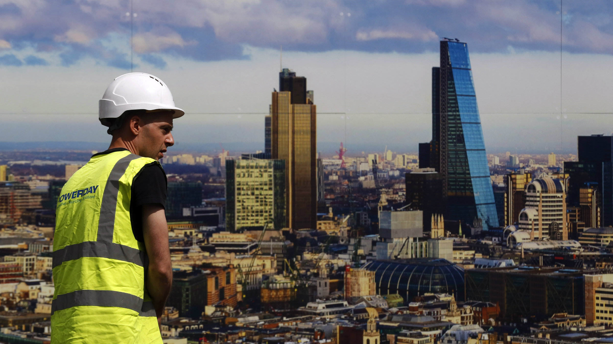 A worker walks past a picture of the London skyline outside the sales office of a property development in central London.