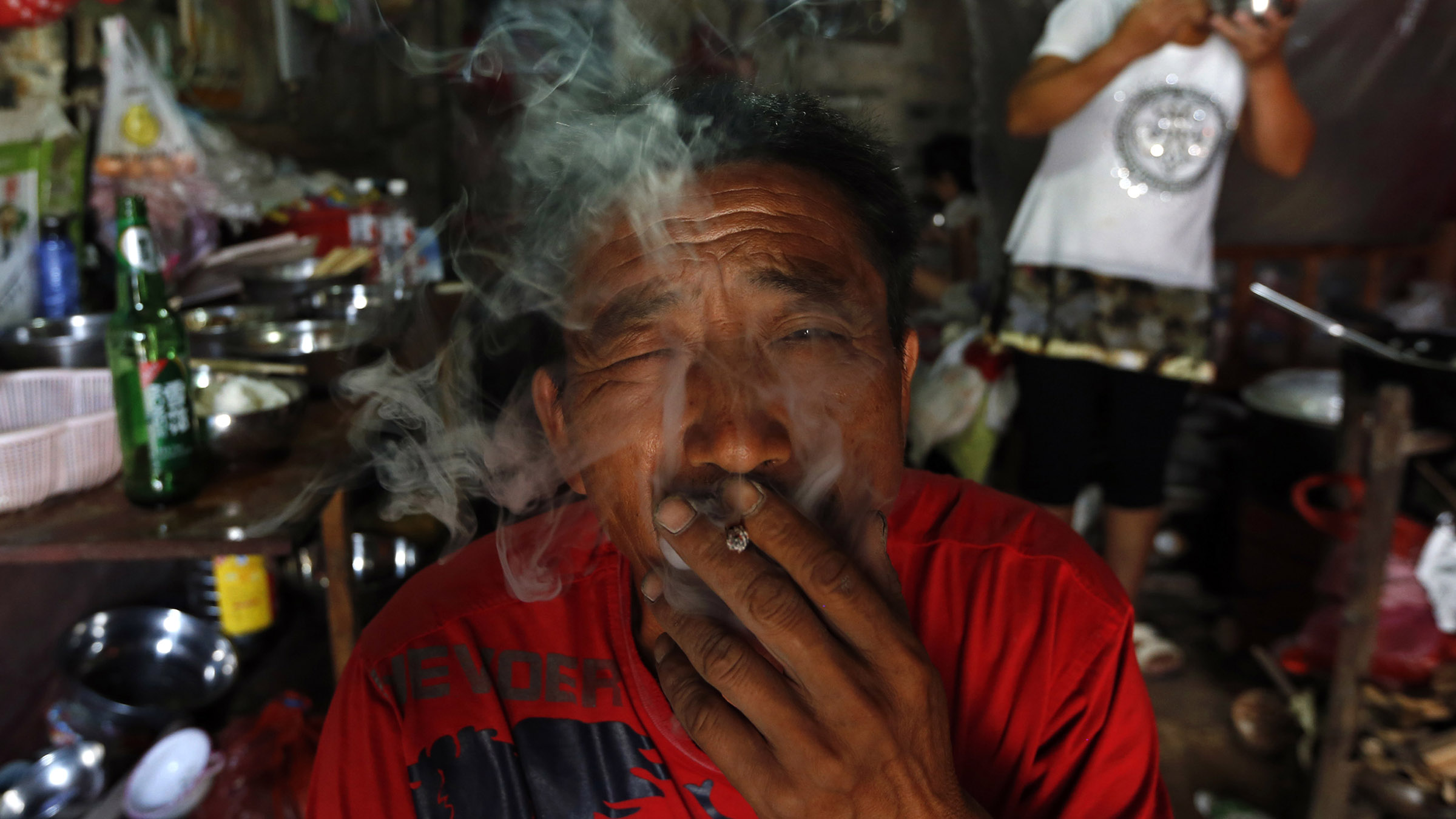 Yang Hongnian, 47, smokes after lunch at home in Jinhua, Zhejiang province, August 7, 2014. Migrant worker Yang, his wife Le Huimin, and their seven children share a 20-square-metre makeshift  house on the outskirts of Jinhua, and live on around 3000-4000 yuan ($486.8-$649) which Yang earns from working at a construction site. Except for one daughter Le had with her ex-husband, the couple have given birth to six children in 10 years. REUTERS/William Hong (CHINA - Tags: SOCIETY) CHINA OUT. NO COMMERCIAL OR EDITORIAL SALES IN CHINA - RTR41K9C