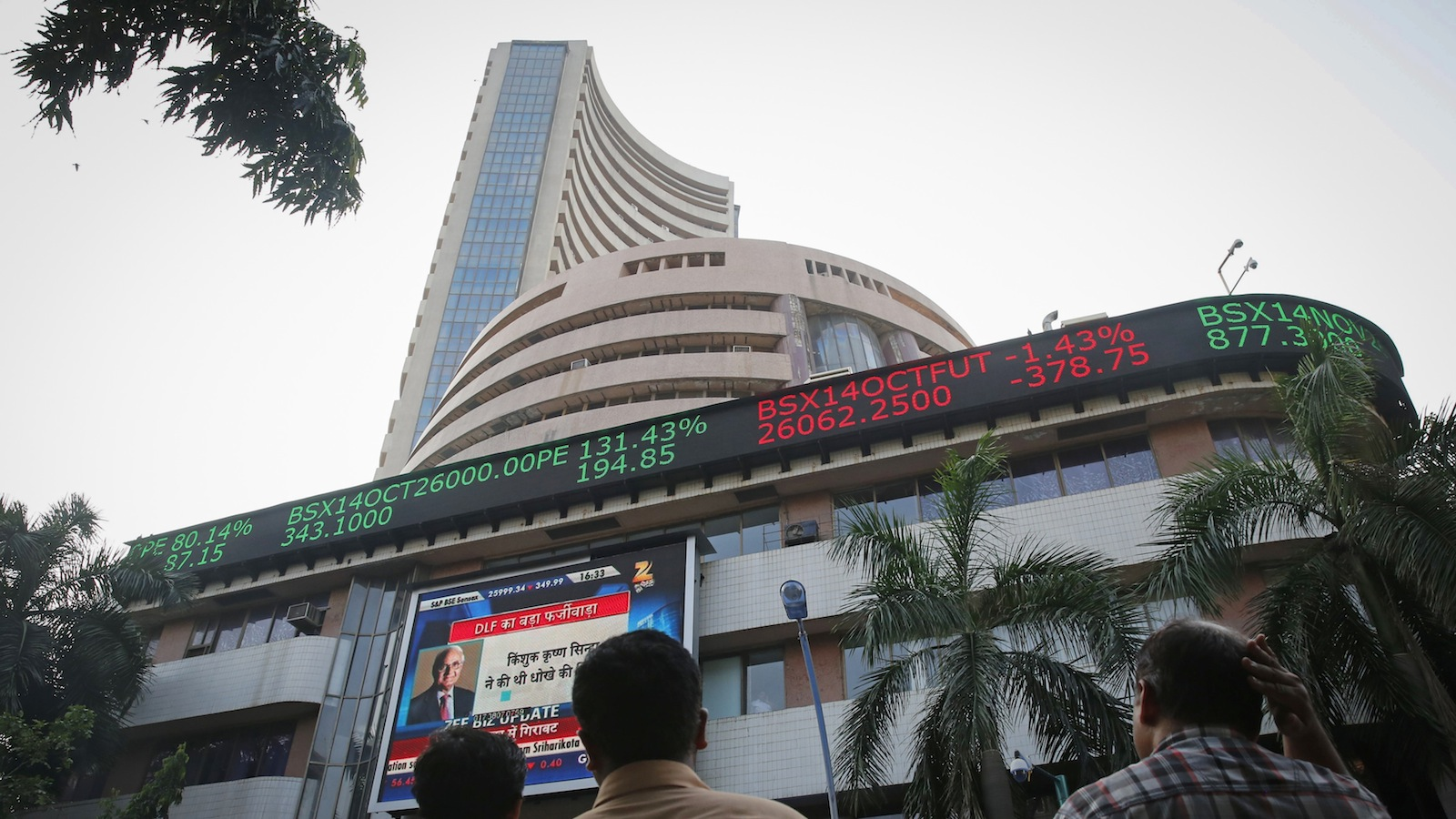 People watch a large screen displaying India's benchmark share index on the facade of the Bombay Stock Exchange (BSE) building in Mumbai October 16, 2014. Indian shares fell for a second consecutive session on Thursday, as companies seen most exposed to the global economy such as Hindalco Industries and Sesa Sterlite declined tracking a downturn in global markets.