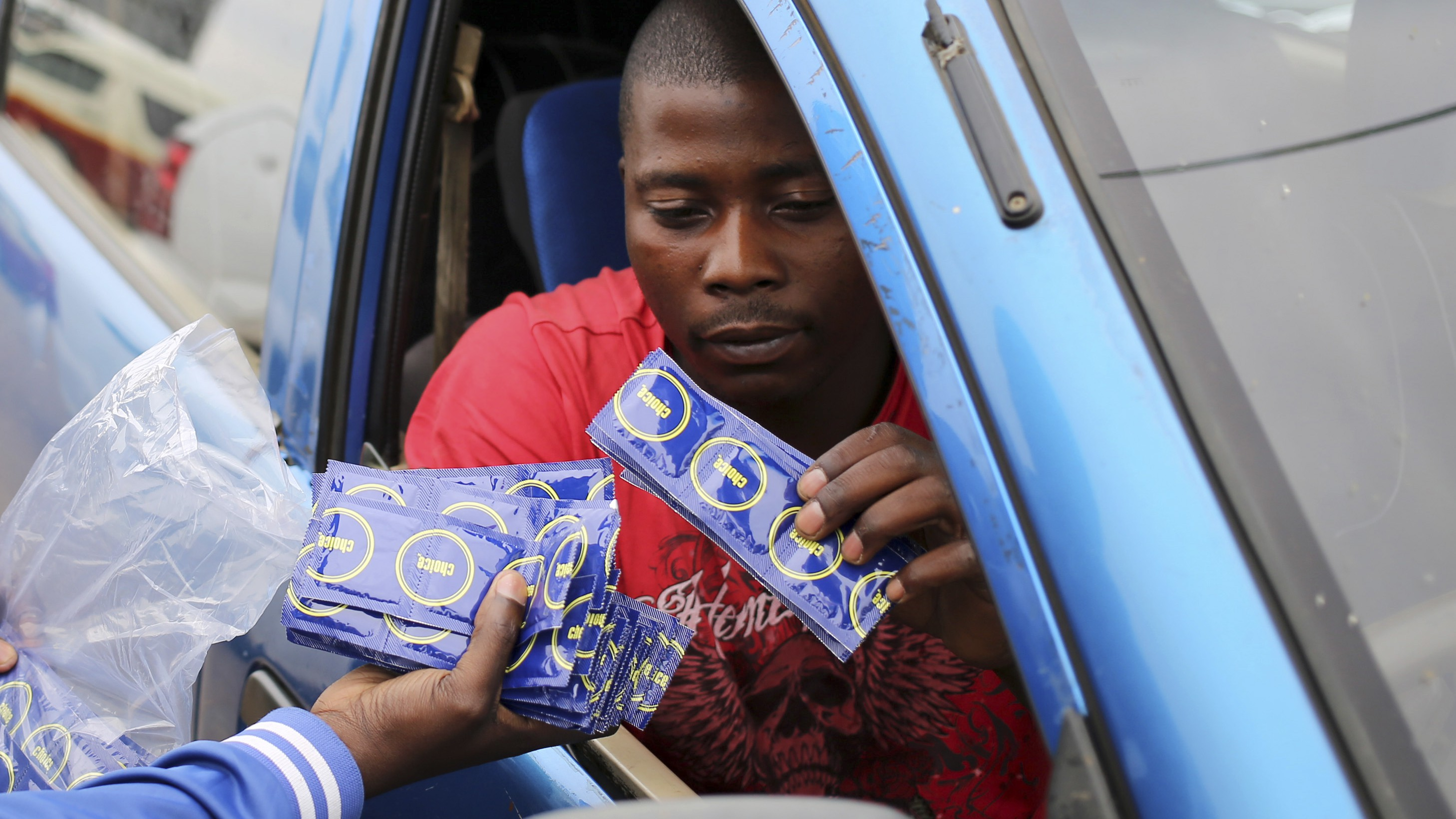 A taxi driver is given condoms by a member of the Treatment Action Campaign (TAC) as they campaign for safe sex in Daveyton, outside Johannesburg November 27, 2014. The activists on the streets of Daveyton want to educate people about how HIV is spread and most importantly, how it can be prevented. December 1 is World AIDS Day. Picture taken November 27. REUTERS/Siphiwe Sibeko (SOUTH AFRICA - Tags: HEALTH) - RTR4G665