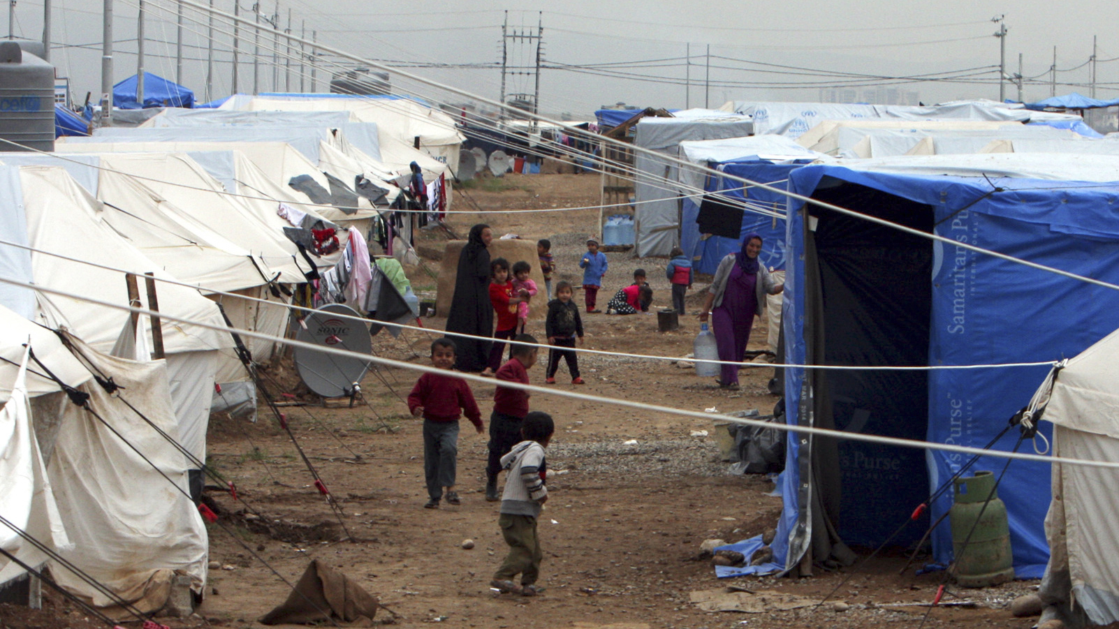 Displaced Iraqi children, who fled from Islamic State violence in Mosul, play in refugee camp on the outskirts of the Kurdish city of Arbil, December 1, 2014.  They used to be symbols of an oil-fuelled boom, but the unfinished buildings in Iraq's Kurdish north are now crammed with people fleeing violence in the rest of the country. Of the two million people displaced by Islamic State offensives in Iraq this year, almost half sought refuge in Kurdistan, inflating the semi-autonomous region's population by around 20 percent and putting acute strain on its resources.
