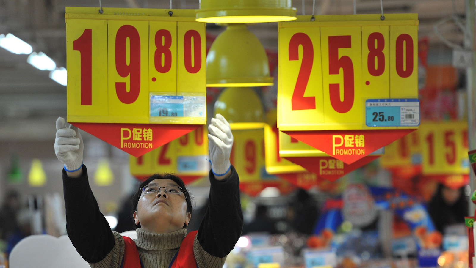 An employee adjusts a price tag at a supermarket in Hefei, Anhui province, January 9, 2015. China's annual consumer inflation was 2 percent in 2014, well below the government's target of 3.5 percent and the number hovered at a near five-year low of 1.5 percent in December, signaling persistent weakness in the economy but giving policymakers more room to ease policy to support growth. REUTERS/Stringer (CHINA - Tags: BUSINESS FOOD SOCIETY) CHINA OUT. NO COMMERCIAL OR EDITORIAL SALES IN CHINA - RTR4KNS6