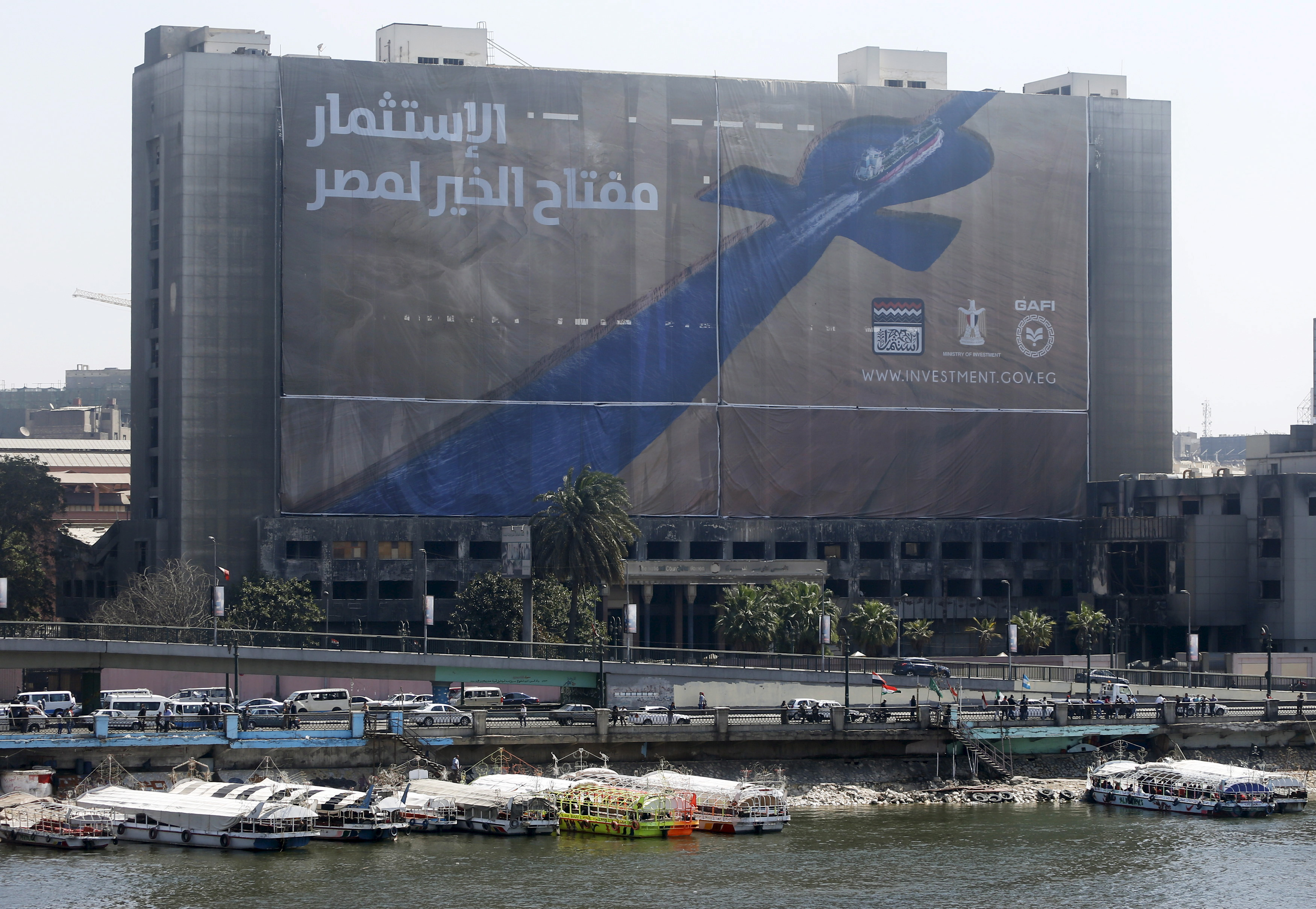 """Boats are docked at the river Nile in front of the burned down headquarters of the National Democratic Party of toppled President Hosni Mubarak in Cairo March 22, 2015. The building, which was burned and gutted during the 2011 uprising, is draped with a banner reading """"Investment is the key to Egypt's prosperity.""""  World Water Day is observed on March 22. REUTERS/Amr Abdallah Dalsh - RTR4UD75"""
