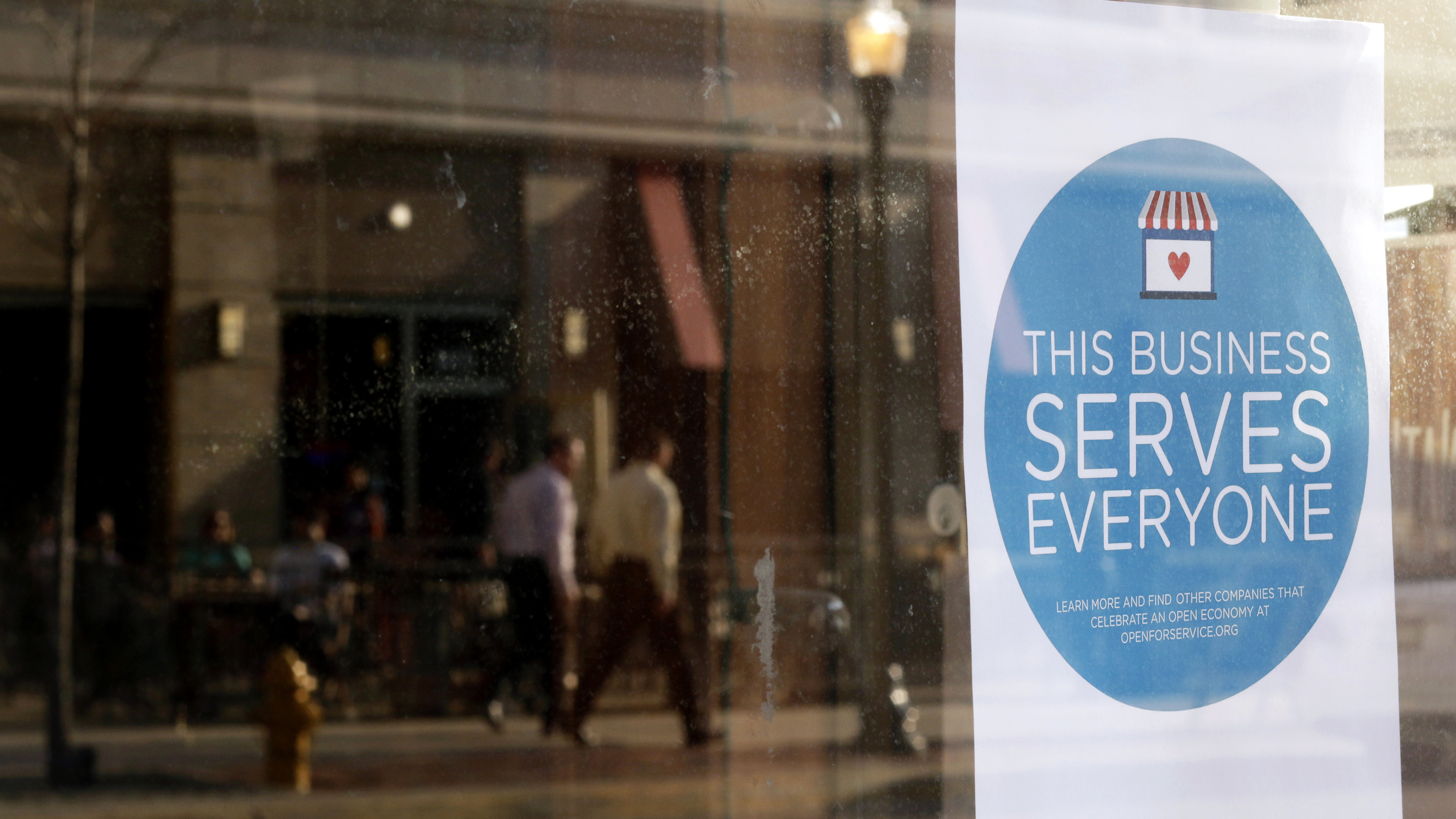 """A sign reading """"This business serves everyone"""" is placed in the window of Bernadette's Barbershop in downtown Lafayette, Indiana March 31, 2015. The store is one of several who display a sticker stating """"This business serves everyone."""""""