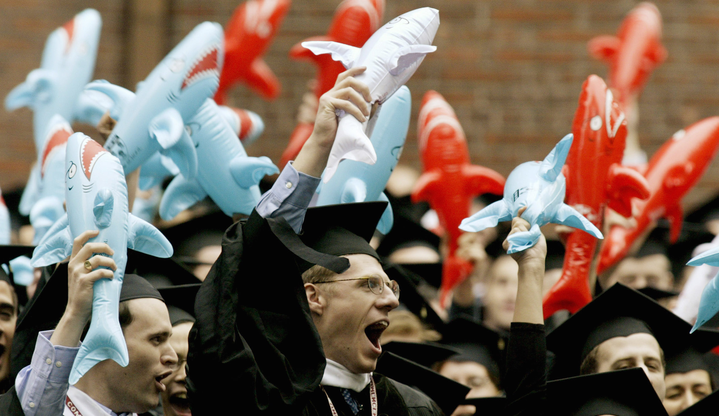 Harvard University Law School graduates mock the reputation of their profession by waving inflatable sharks as their degrees are conferred during commencement ceremonies in Harvard Yard in Cambridge, Massachusetts, June 5, 2003. REUTERS/Jim Bourg  JRB - RTROWQM