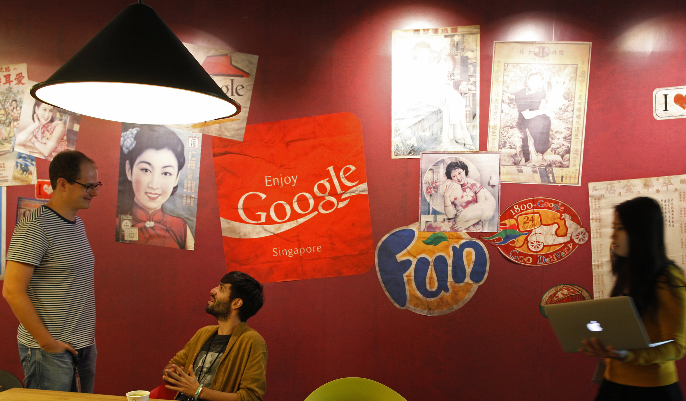 "Google's communications manager Robin Moroney (L) speaks to employees at a pantry decorated with vintage Singapore advertisements and signages in their Singapore office July 8, 2013. Singapore's move to tighten regulation of news web sites, already under fire from bloggers and human rights groups, has attracted criticism from an unexpected quarter - large internet firms with a big presence in the city-state who say the new rules will hurt the industry. Web giants Facebook Inc, eBay Inc, Google Inc and Yahoo! Inc have said the revised rules ""have negatively impacted Singapore's global image as an open and business-friendly country"". REUTERS/Edgar Su (SINGAPORE - Tags: MEDIA BUSINESS POLITICS SCIENCE TECHNOLOGY) - RTX11GDD"
